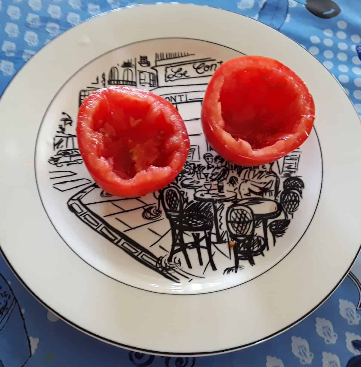 Roma tomato cut in halve and hollowed out on white plate.
