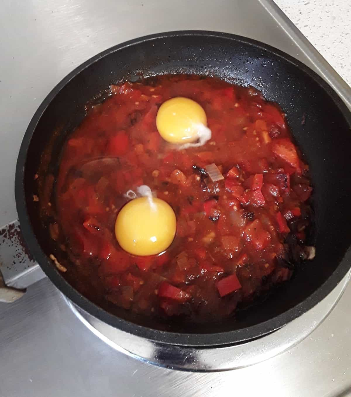 Cooking two eggs in skillet with marinara sauce.