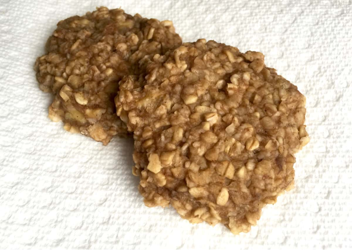 Two banana oat cookies on white paper towel.