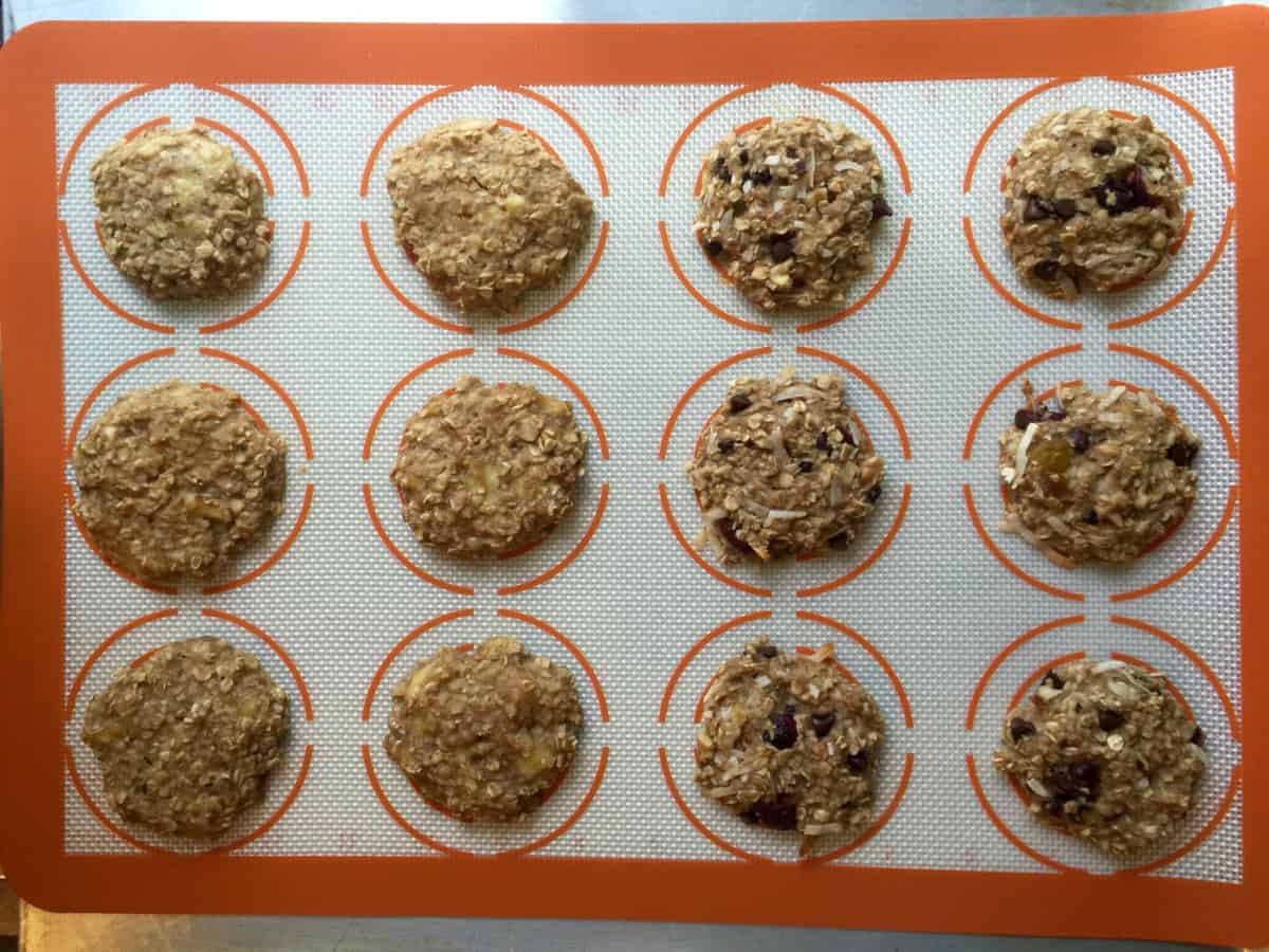 Baked oatmeal cookies on silat-lined baking sheet.