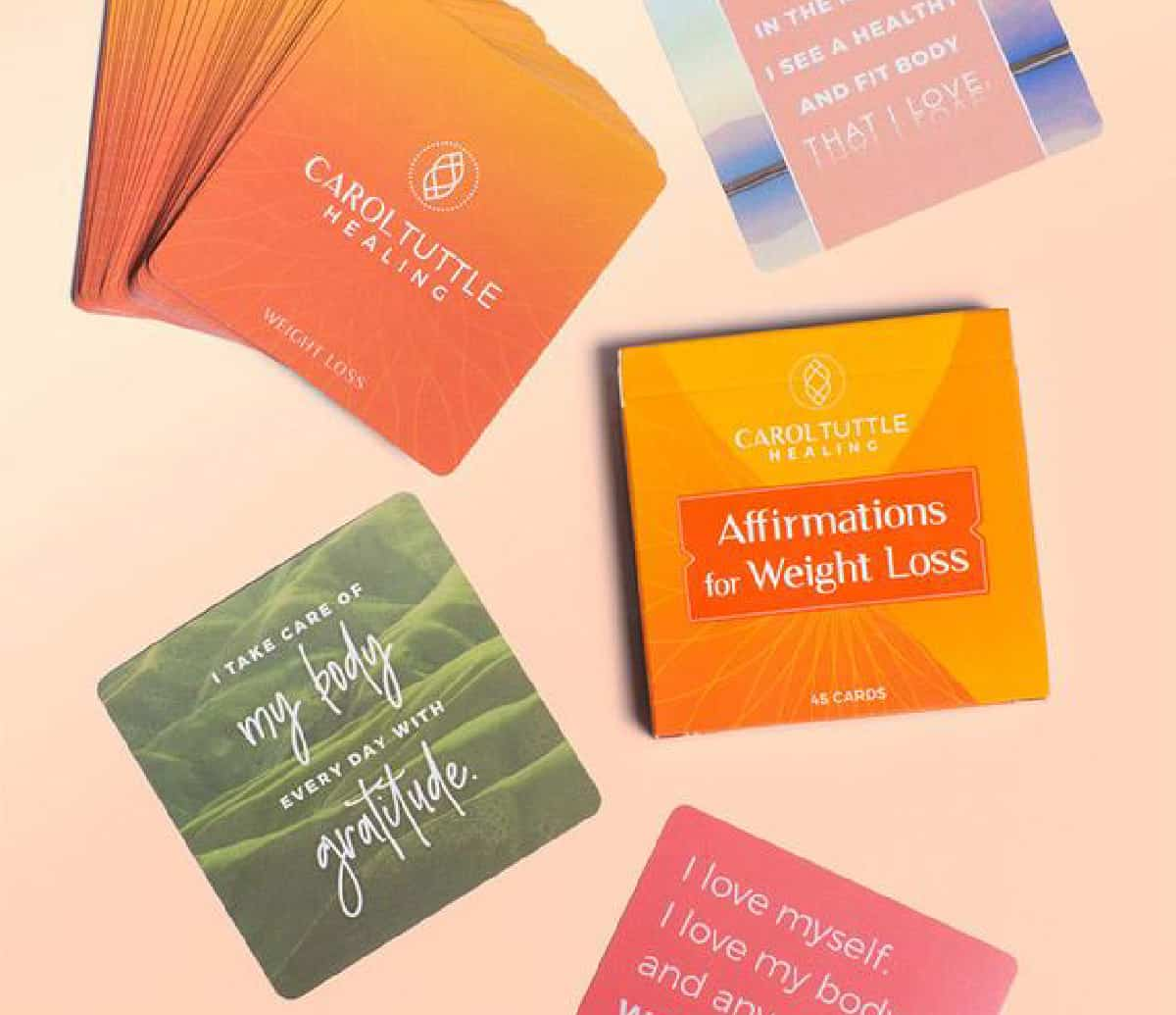 Weight loss affirmation cards from Carol Tuttle scattered on a table