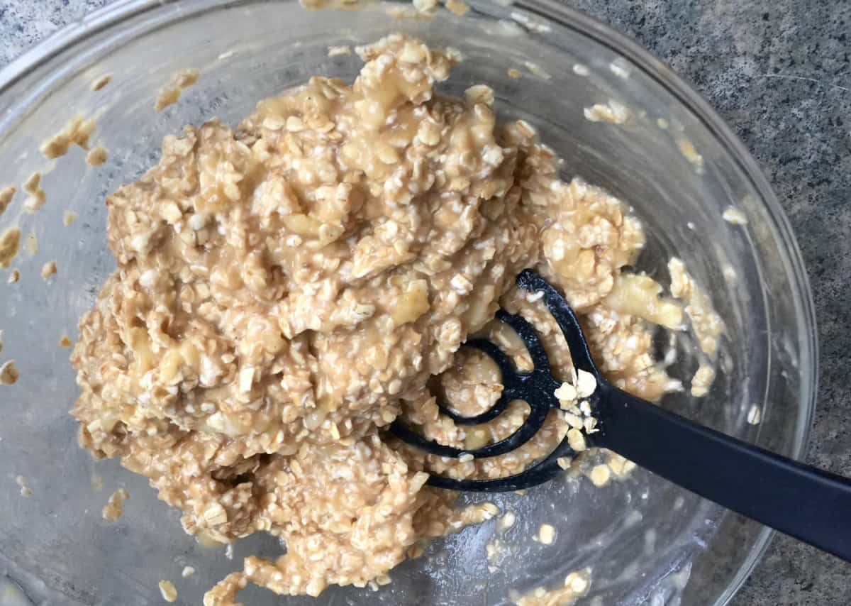 Mashing ripe bananas with rolled oats in glass bowl.