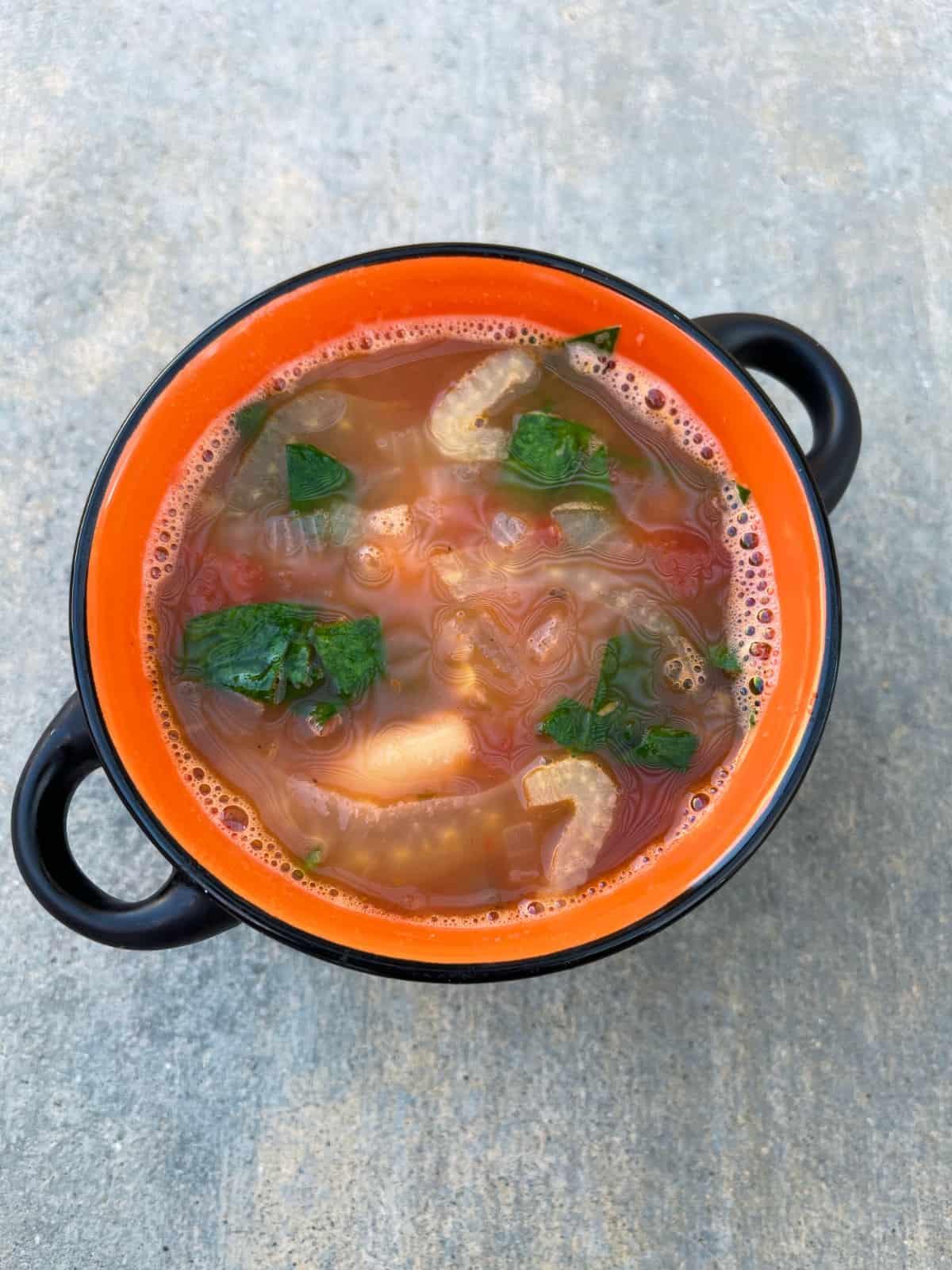Fennel white bean soup in orange soup crock.
