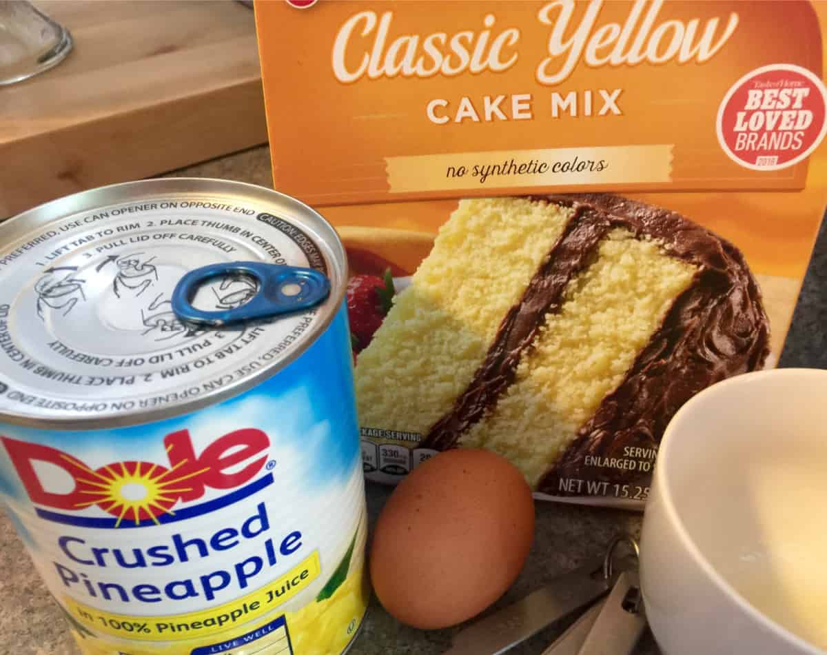 Box of yellow cake mix, can of Dole crushed pineapple, egg and a mug.