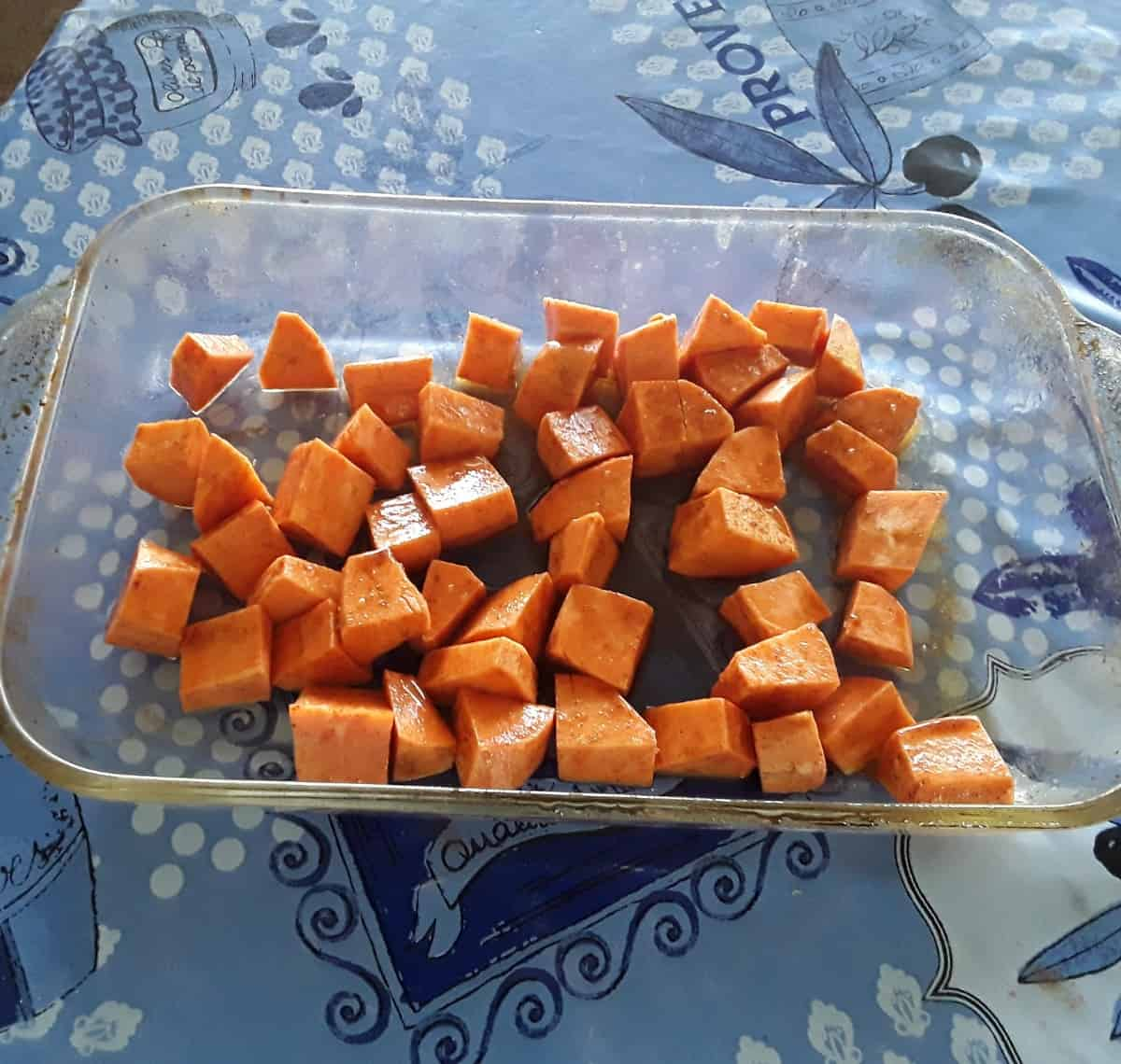 Uncooked chopped sweet potatoes in glass baking dish.