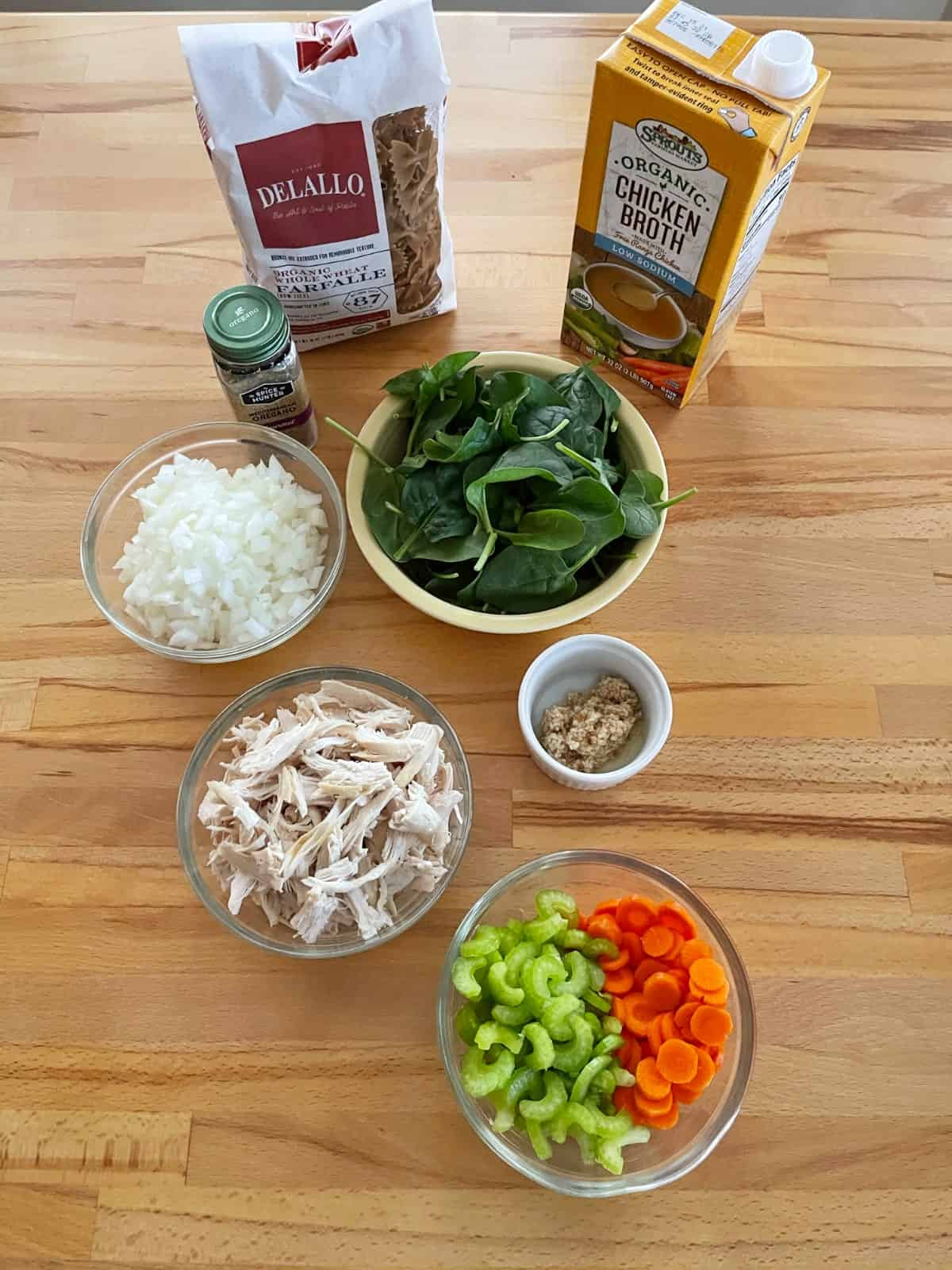 Ingredients for making soup including dry pasta, chicken broth, spinach, onion, chicken, celery, carrots and garlic.