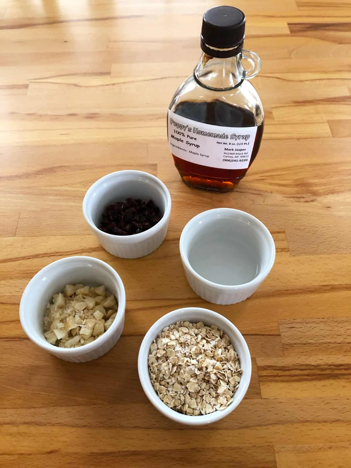 Ingredients for making granola, including maple syrup, oats, coconut oil, raisins and chopped macadamia nuts.