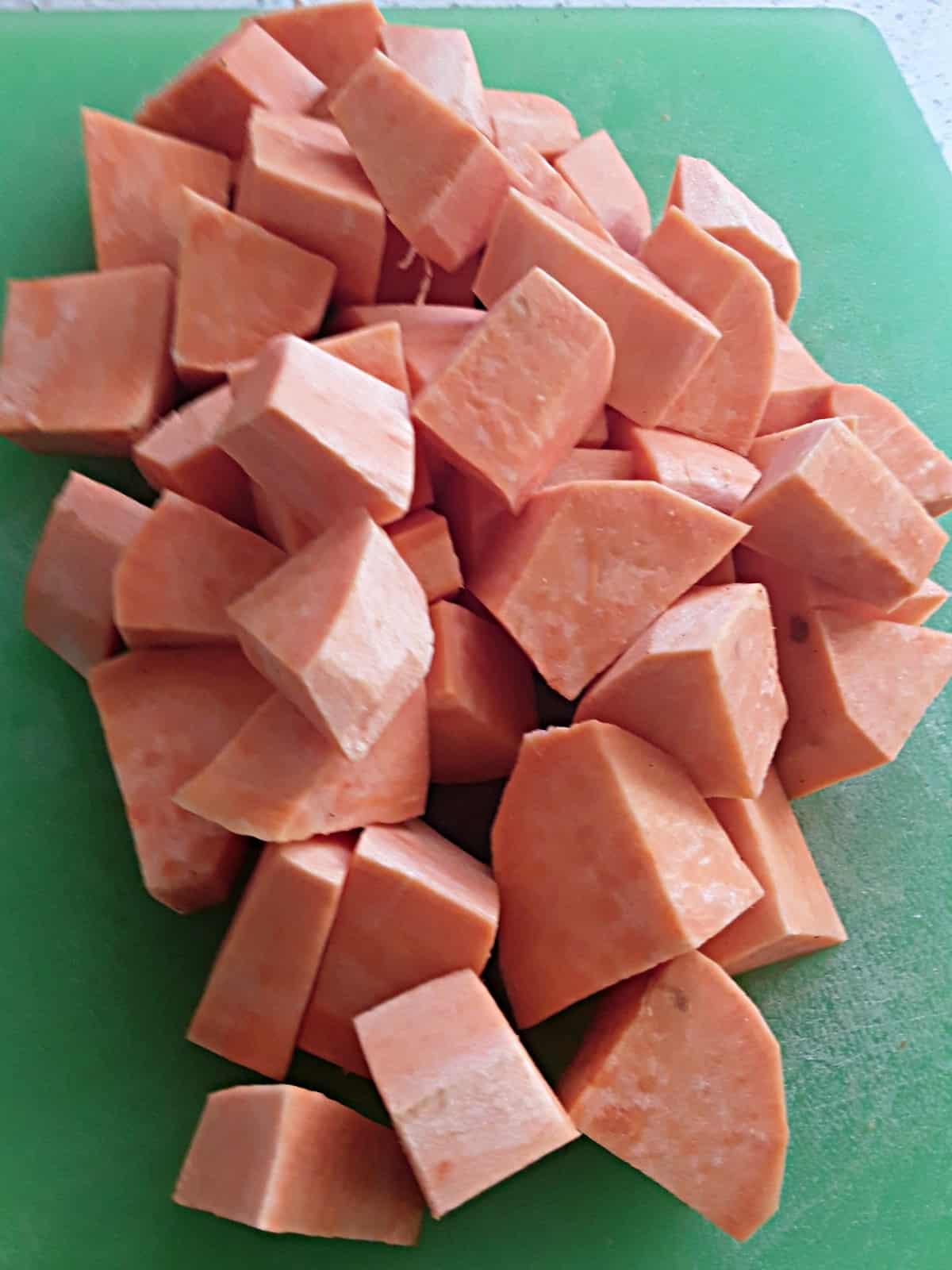 Peeled and chopped sweet potatoes on green cutting board.