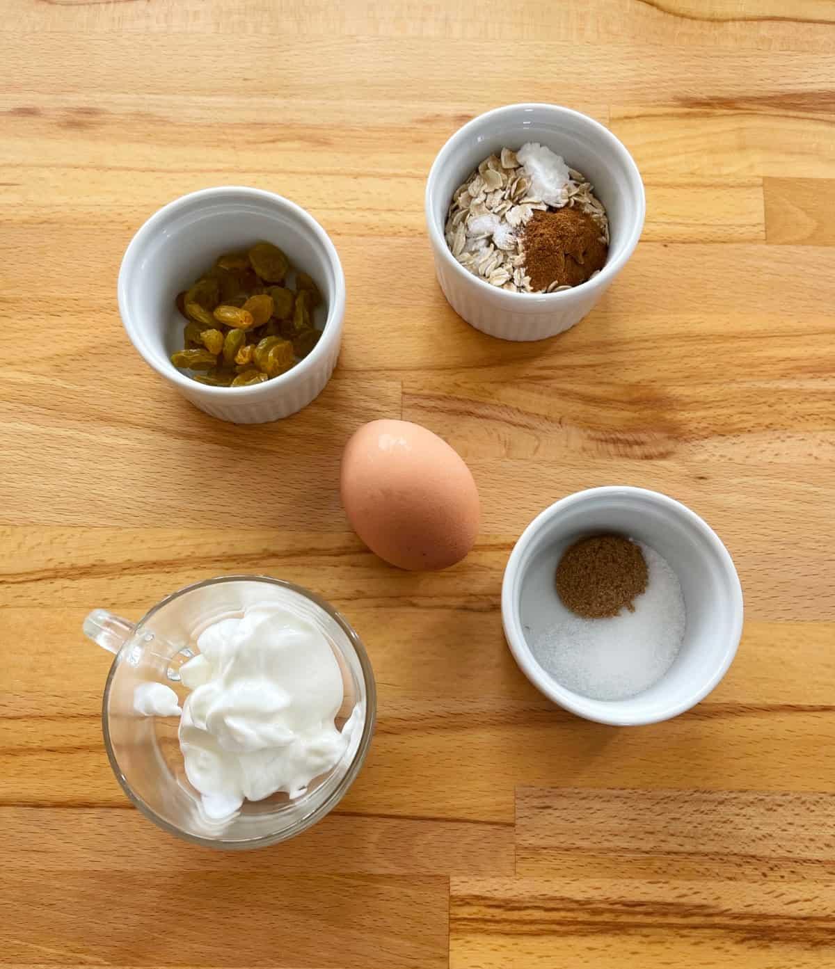 Ingredients for making microwave muffin including oats, cinnamon, raisins, egg, Greek yogurt and sugar an small white ramekins.