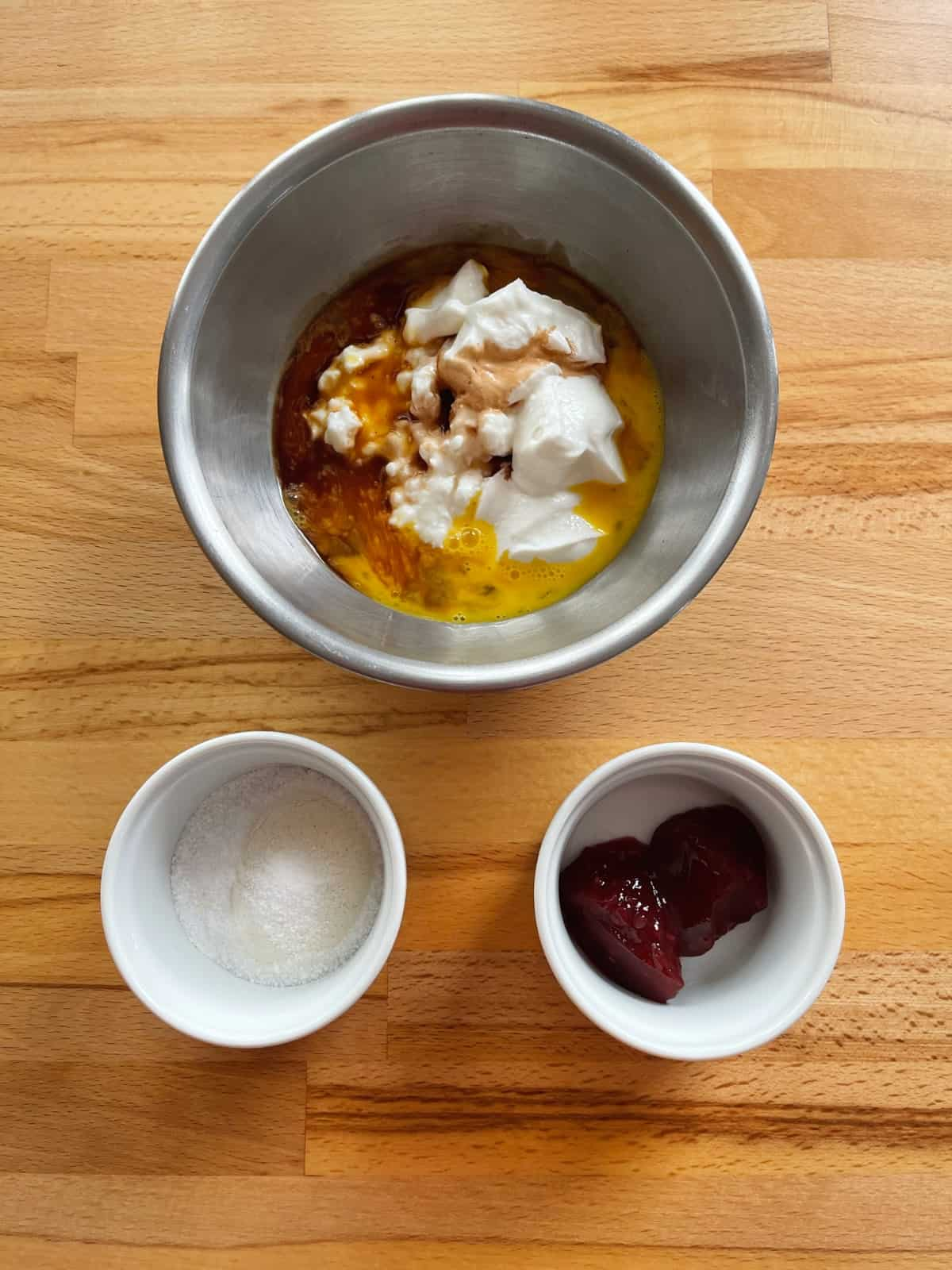 Mixing bowl with yogurt, cottage cheese, egg, vanilla and ramekins with flour sugar and raspberry jam on wooden table.