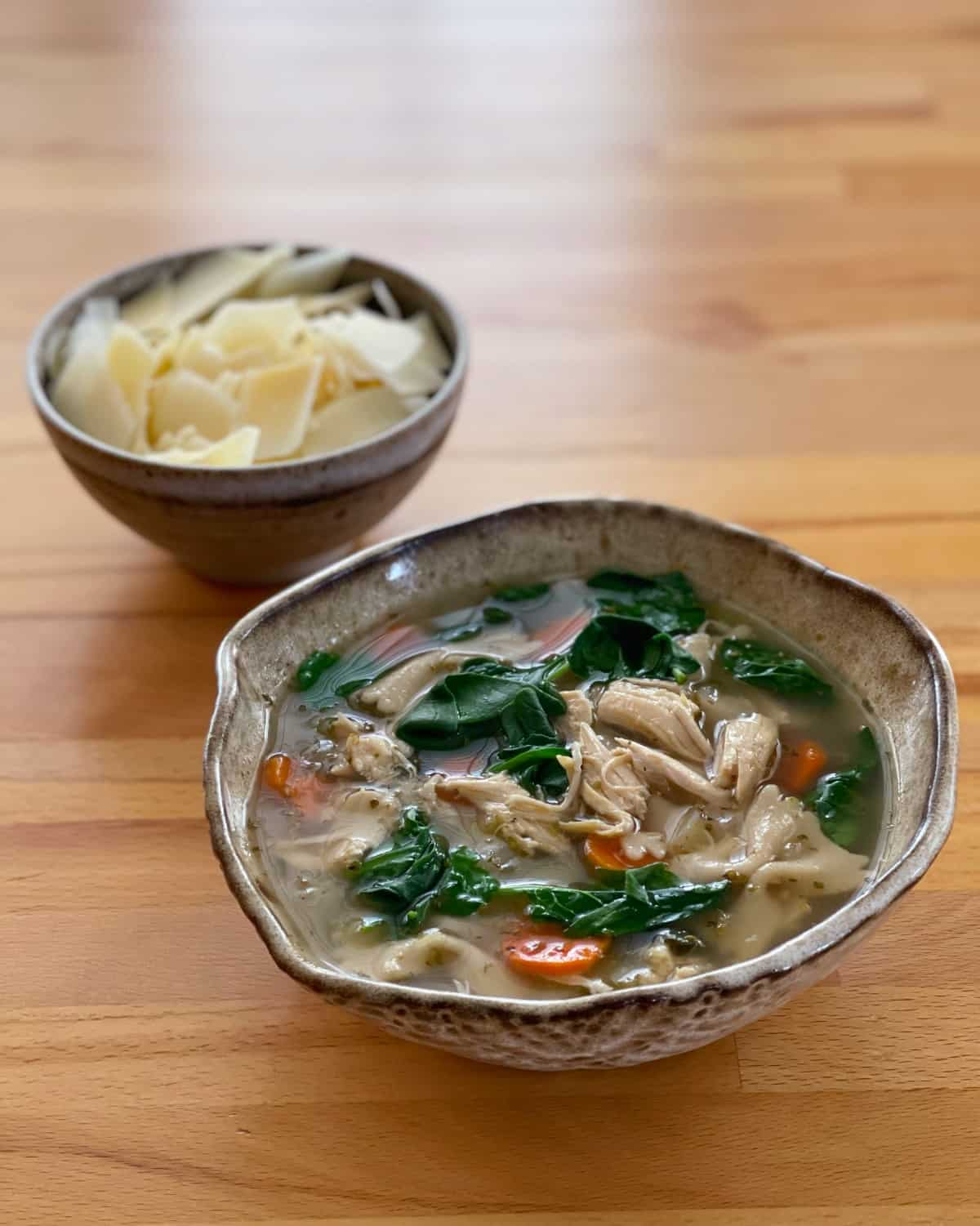 Tuscan chicken bowtie soup in ceramic bowl with small bowl shredded Parmesan cheese