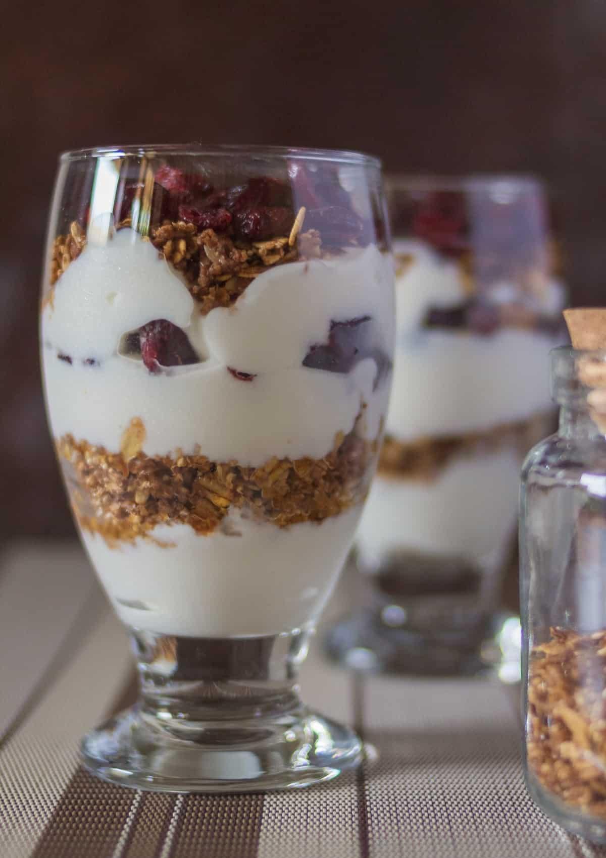 Yogurt granola fruit parfait in tall glass.