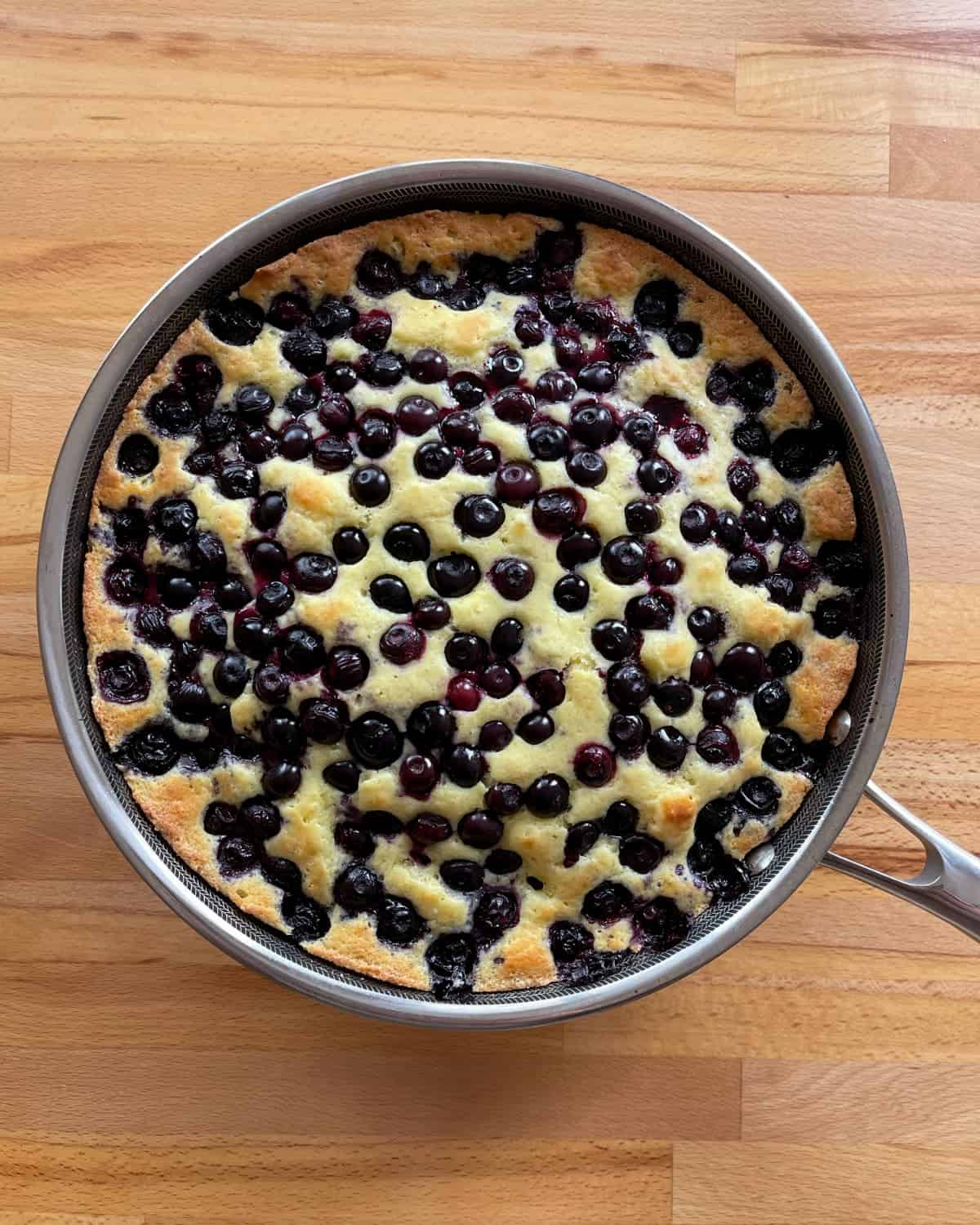 Oven-baked blueberry skillet pancake on wood table.