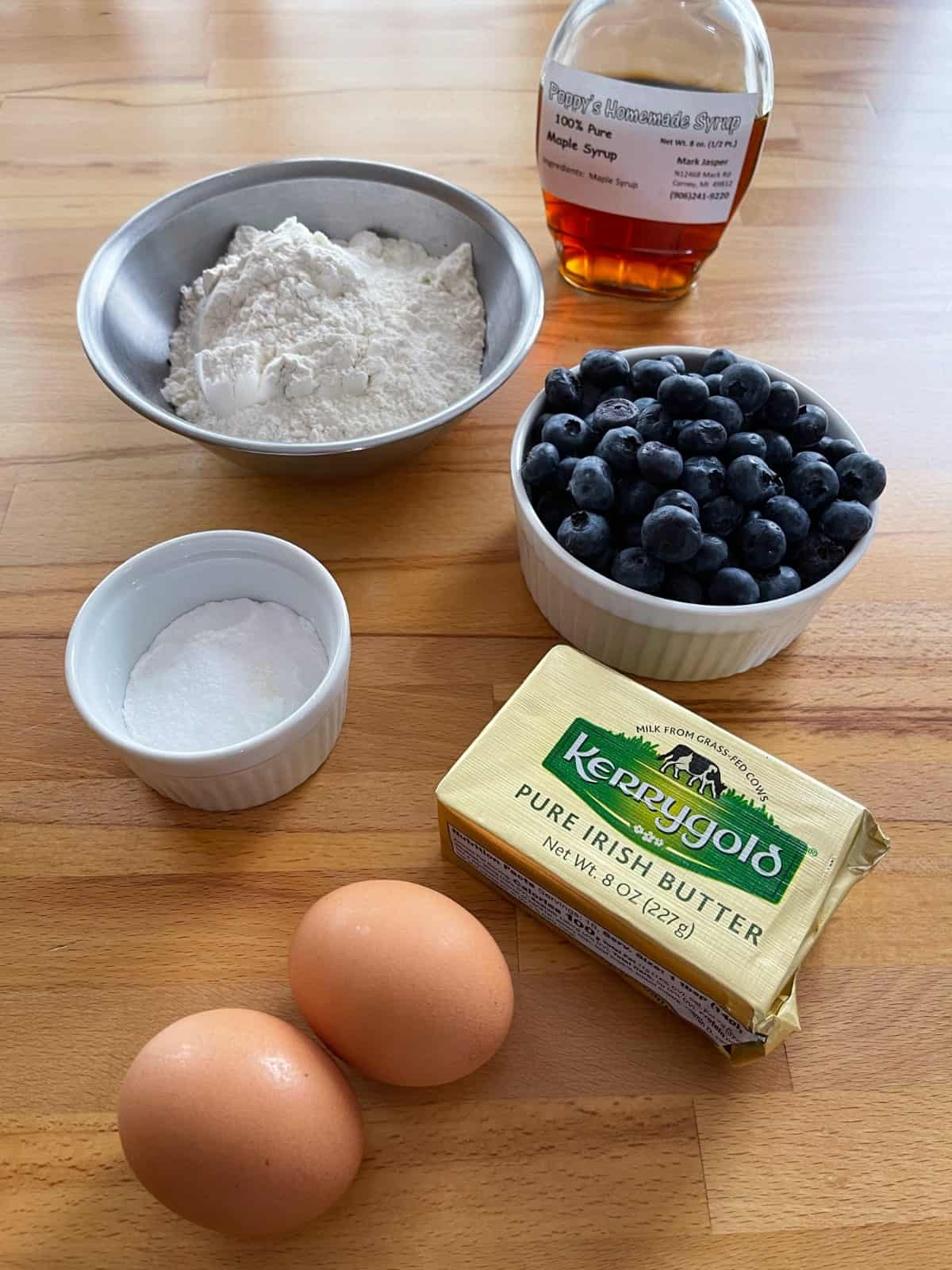 Maple syrup, flour, baking soda, salt, blueberries, butter and eggs on wooden table.
