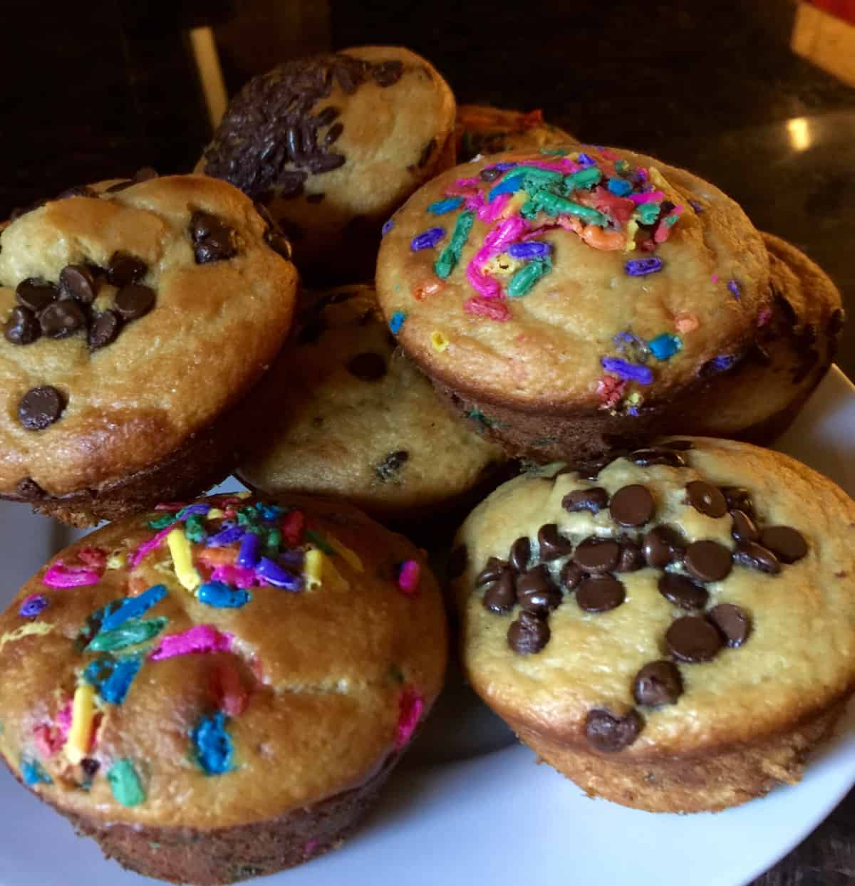 Fresh muffins topped with chocolate chips and colored sprinkles