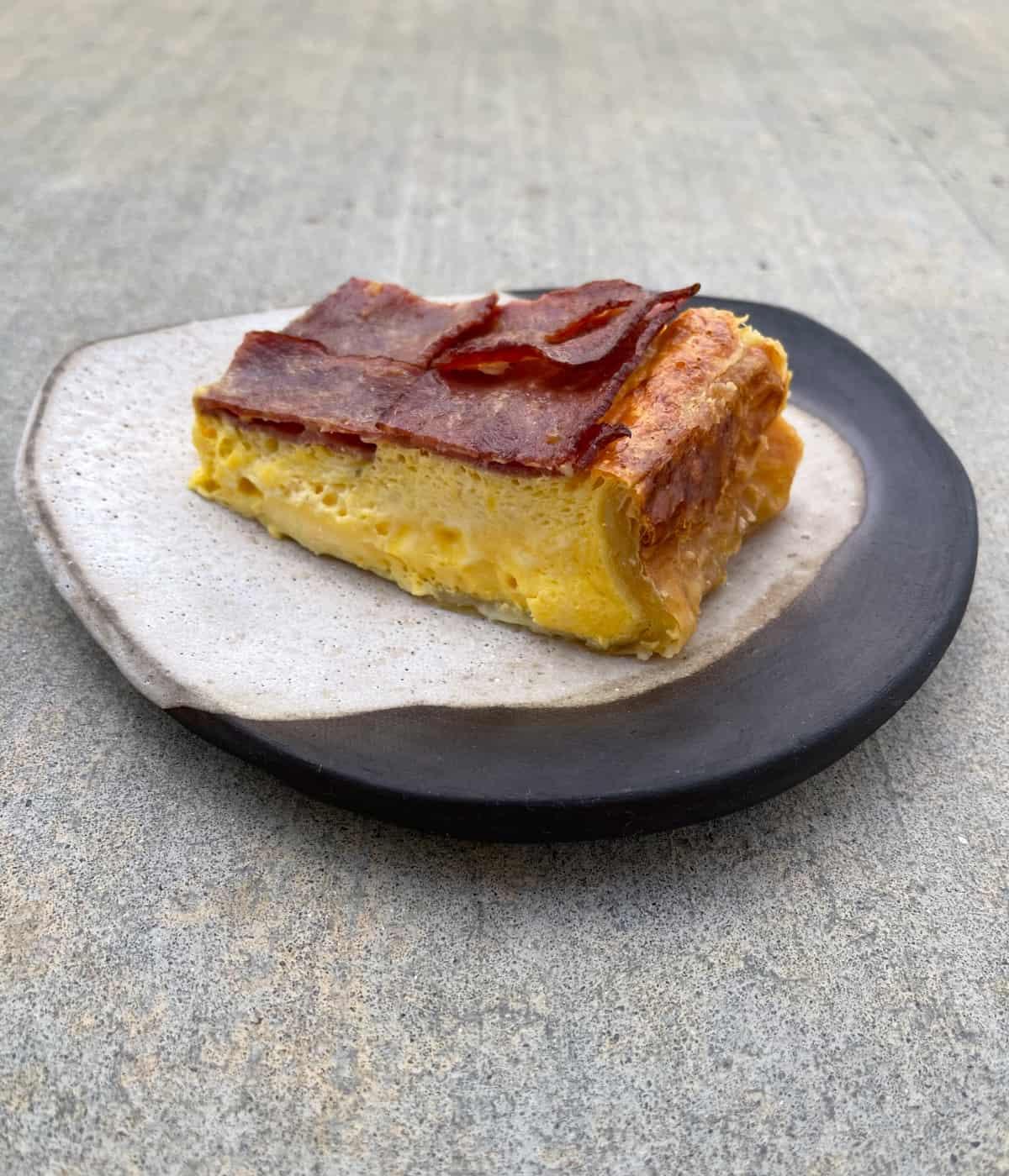 Breakfast pie topped with crispy turkey bacon on ceramic plate.