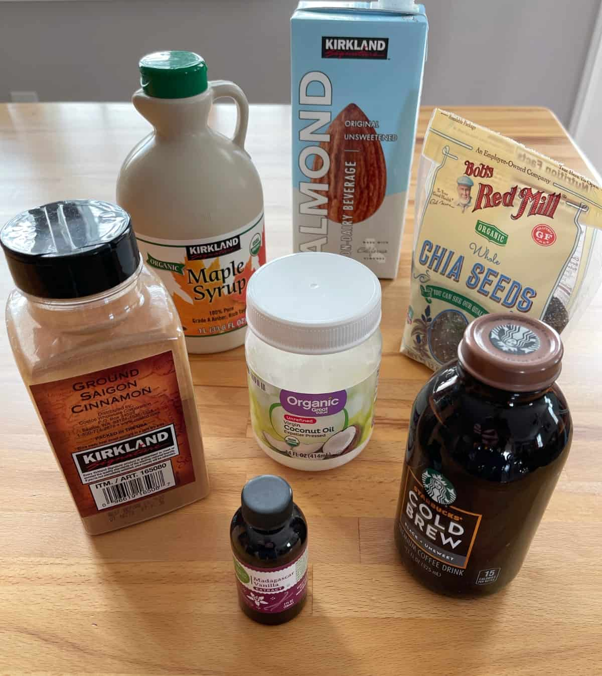 Ingredients for making chia pudding including almond milk, cold brew coffee, cinnamon, chia seeds and maple syrup.