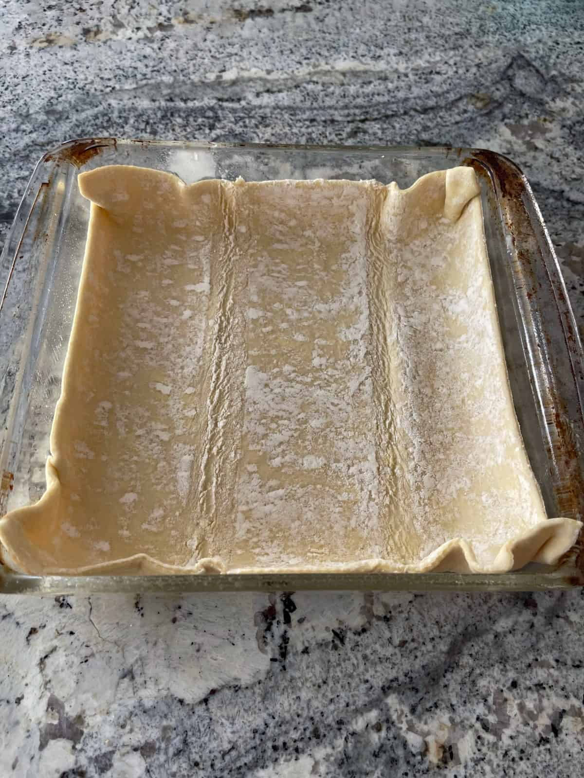 8-inch square glass baking dish with puff pasty sheet on granite counter.