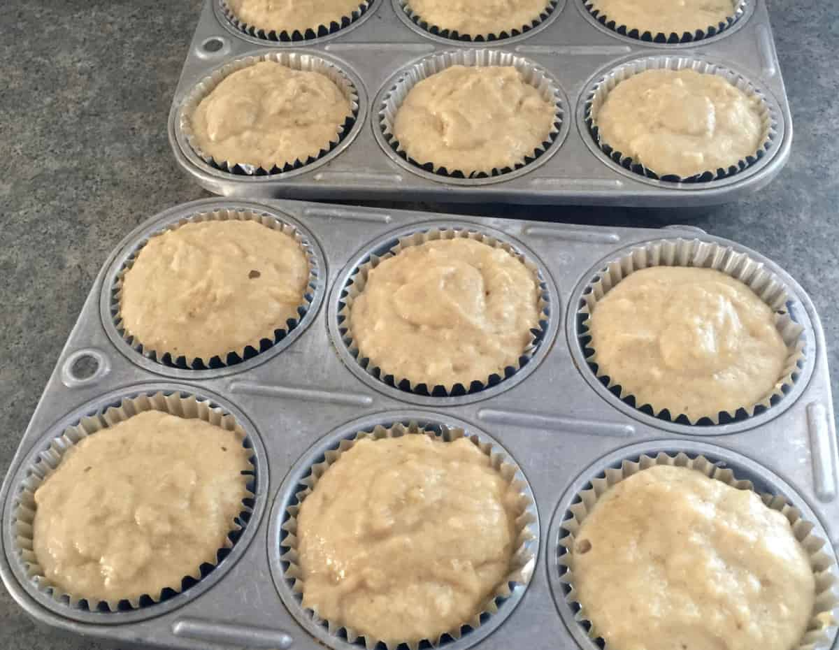 Two 6-muffin muffin tins filled with muffin mix.
