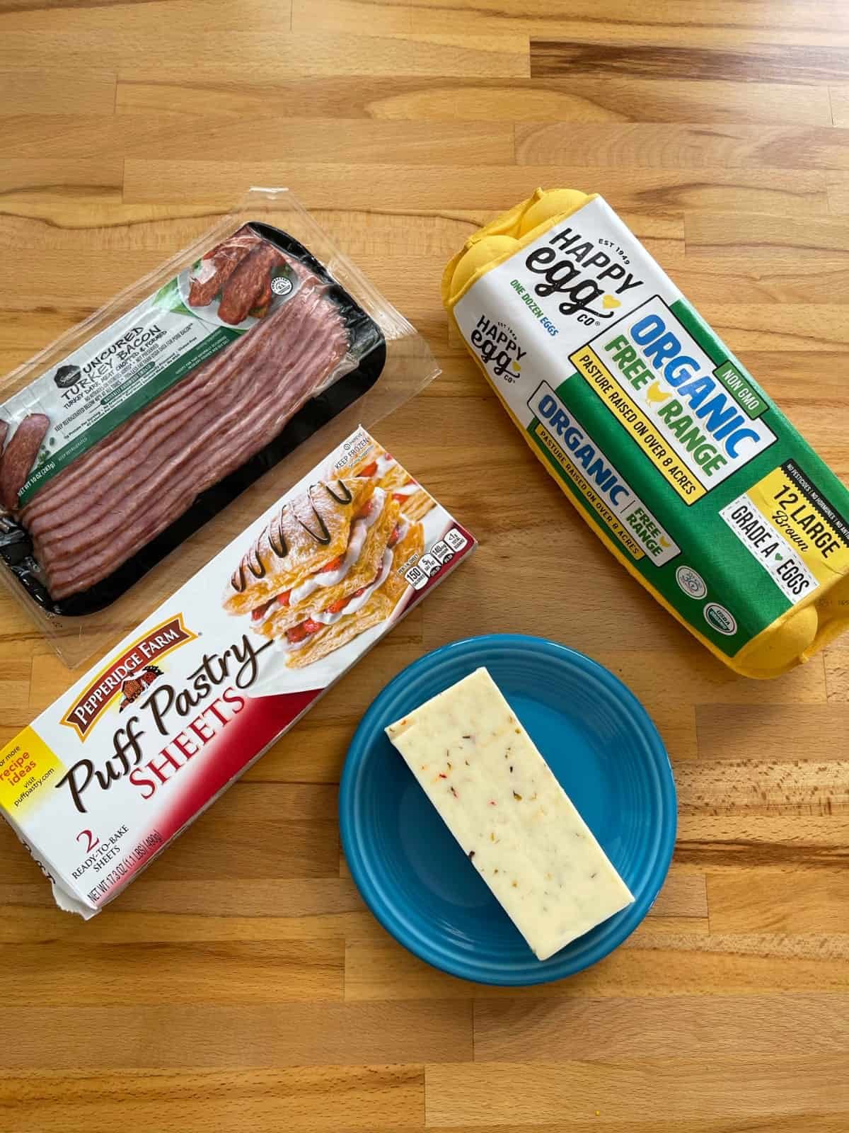 Ingredients for making breakfast pie including turkey bacon, puff pastry sheets, carton of eggs and pepper jack cheese on wood table.