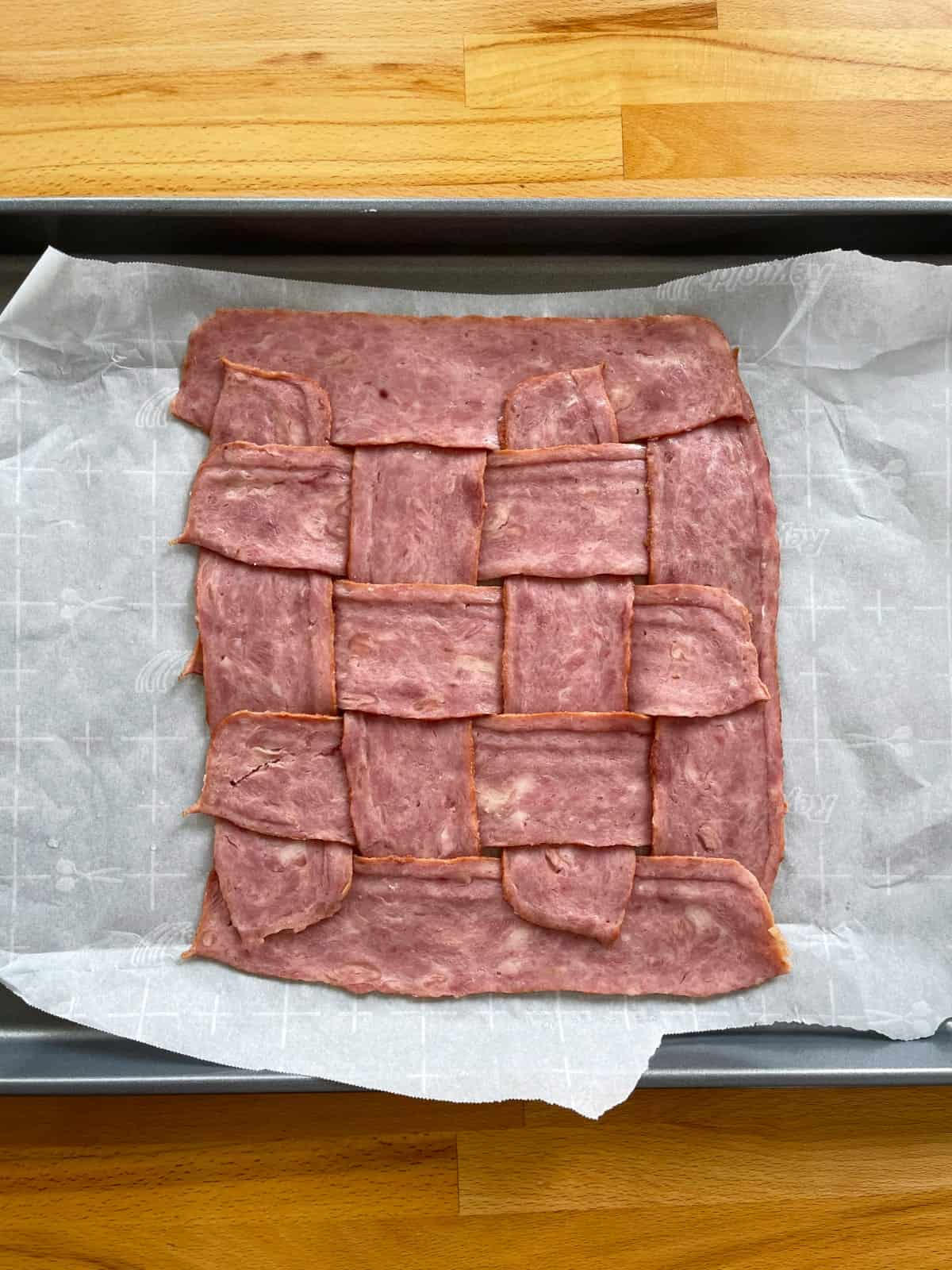 Strips of uncooked turkey bacon woven into lattice on parchment lined baking sheet.