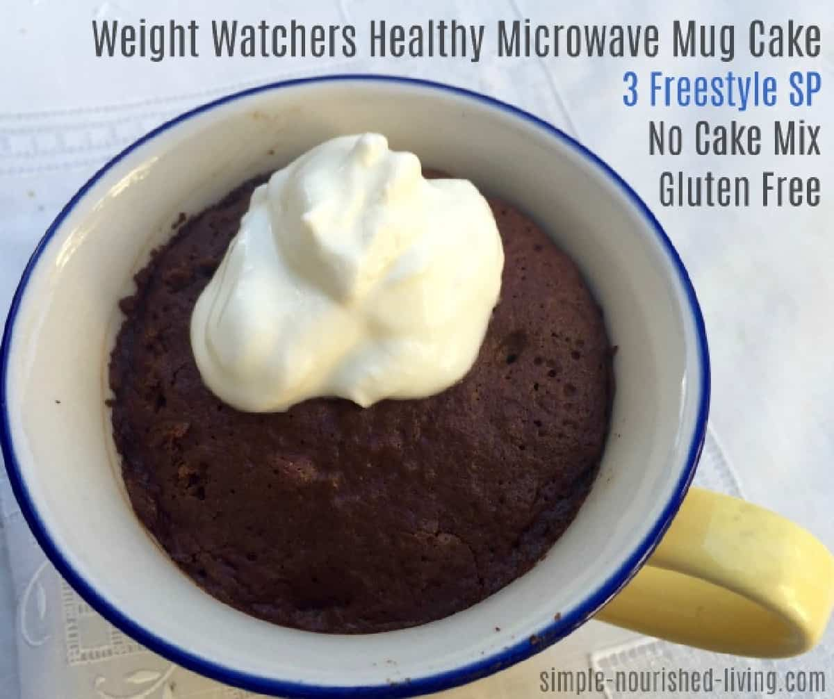 Chocolate microwave mug cake topped with a dollop of whipped topping.