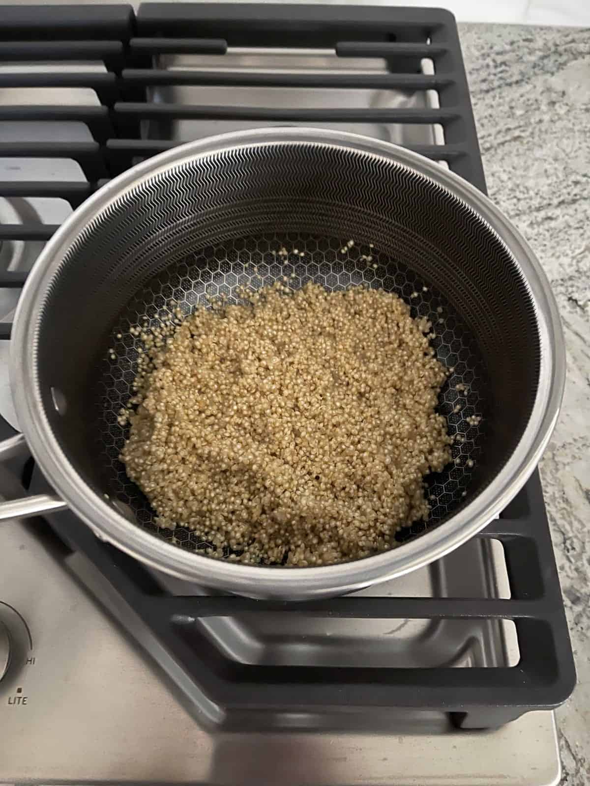 Cooking quinoa in saucepan on stovetop