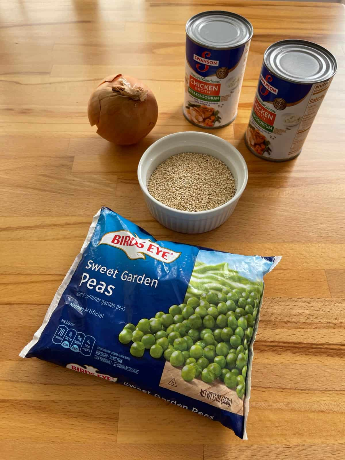 Bag of frozen peas, quinoa, whole onion and two cans of chicken broth for making soup on wood table.