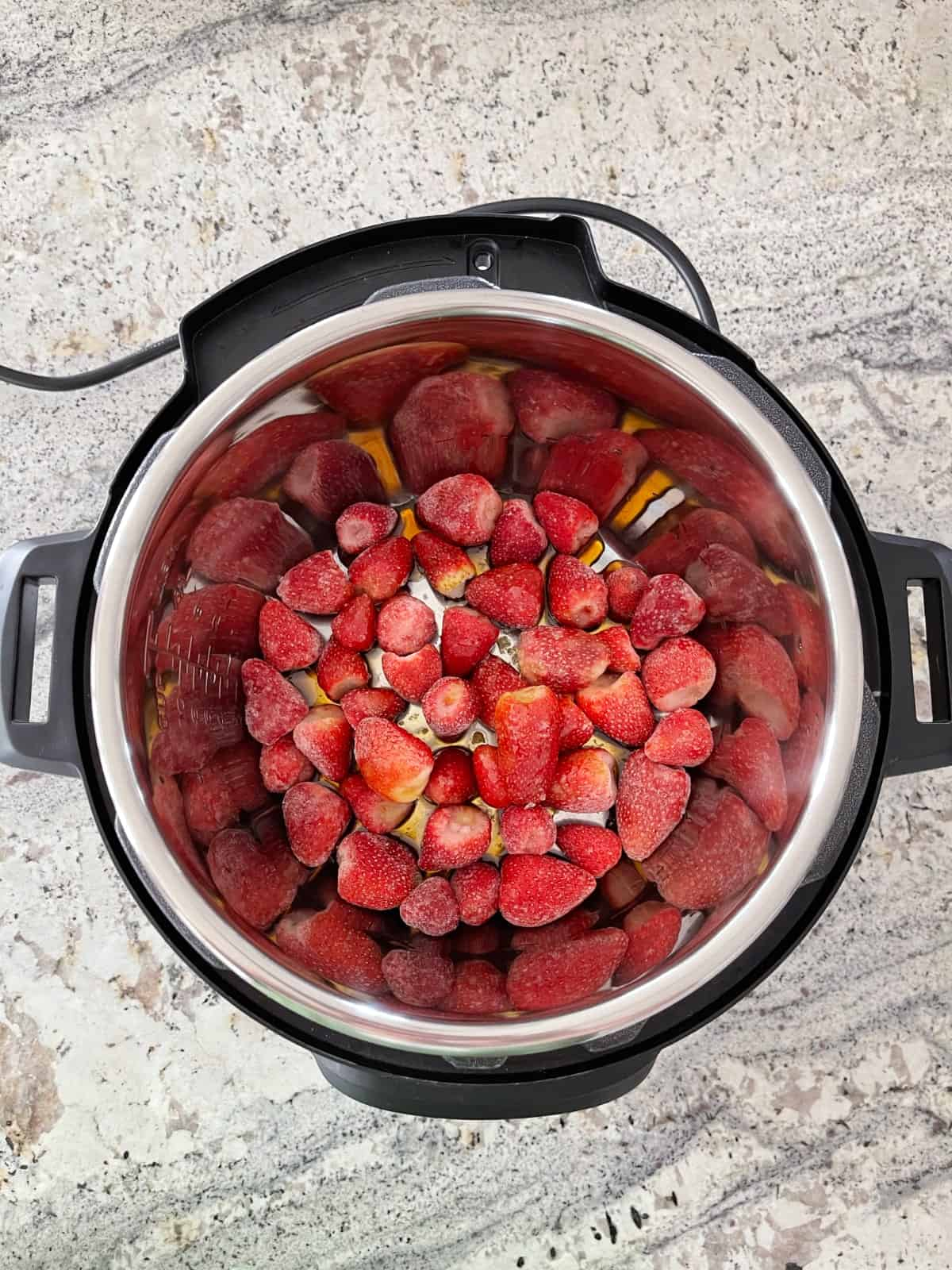 Instant Pot with frozen strawberries and maple syrup on granite counter from above.