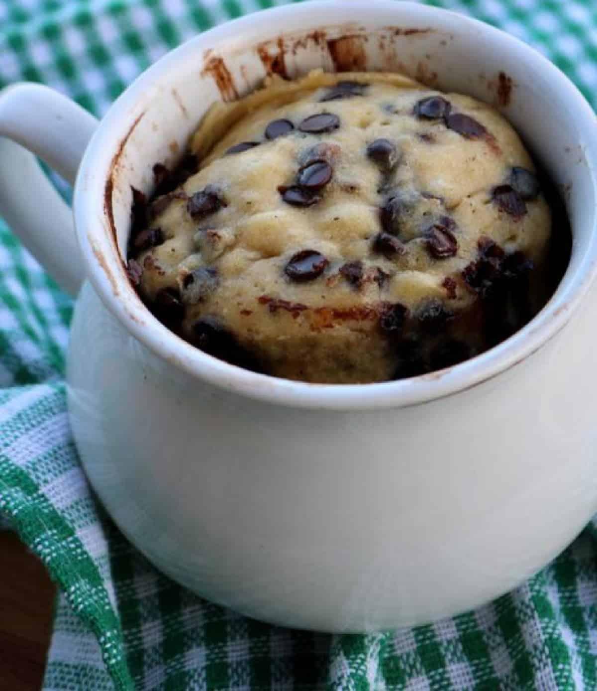 White mug with microwave chocolate chip cookies.