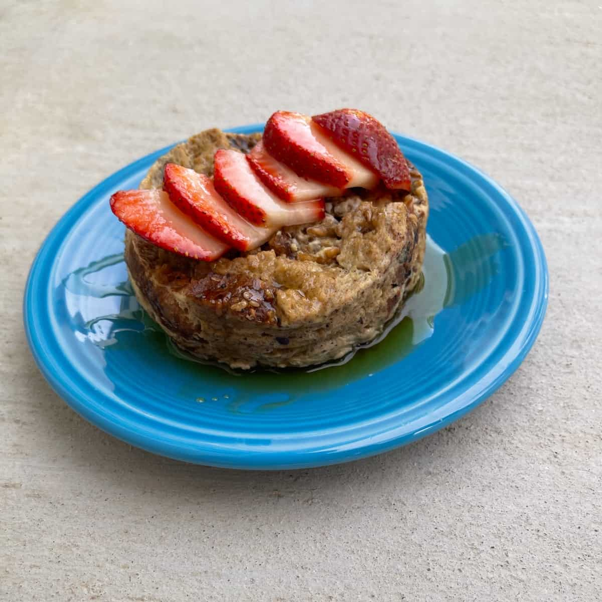 Microwave French toast topped with sliced strawberries and maple syrup on blue plate.