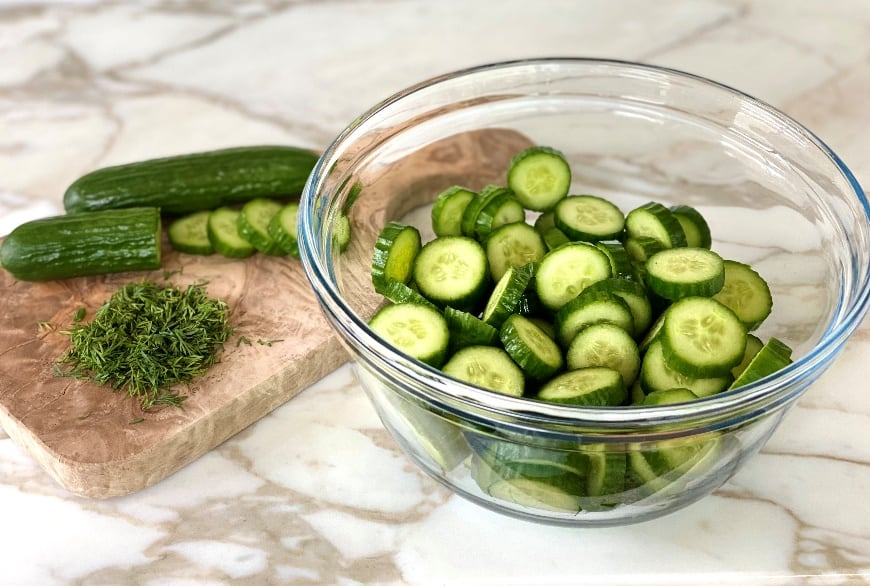 Bowl of cucumber slices near cutting board with cucumbers and spices