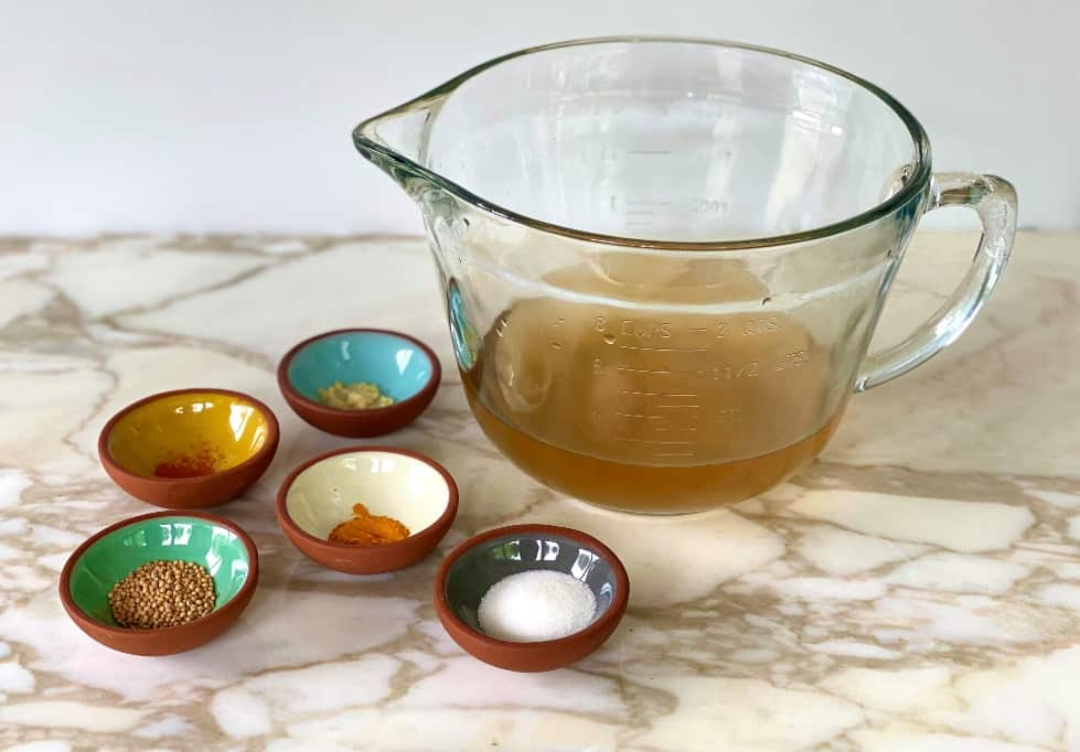 Apple cider vinegar in measuring cup with spices in small dishes.