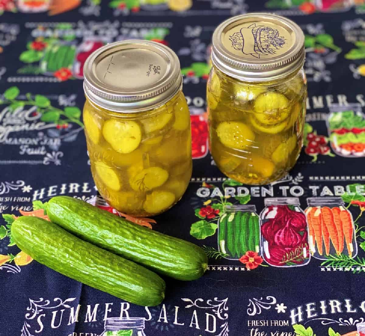 Two mason jars with fresh dill pickles on table with two cucumbers.