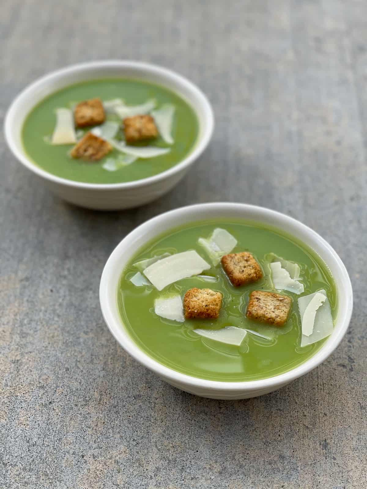 Two bowls of pea soup topped with shaved Parmesan and croutons