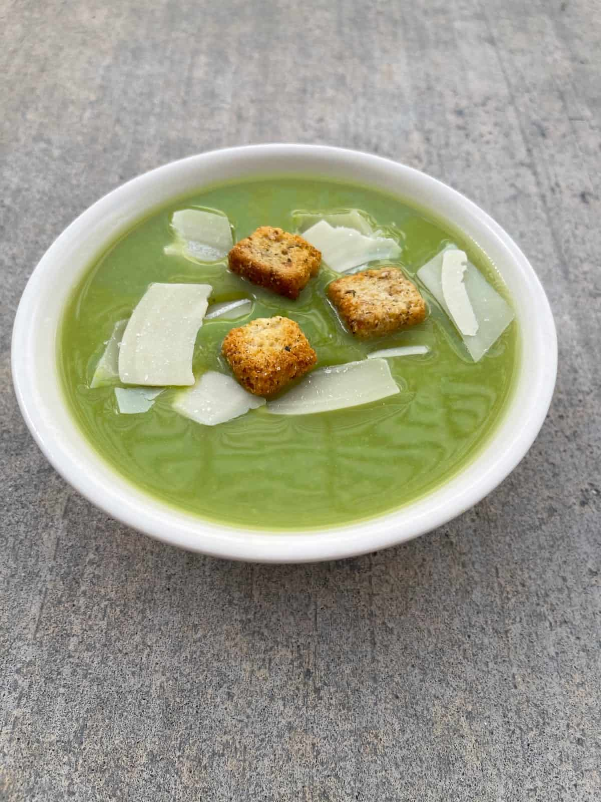 Pea soup with quinoa in white bowl topped with croutons and shaved Parmesan cheese.