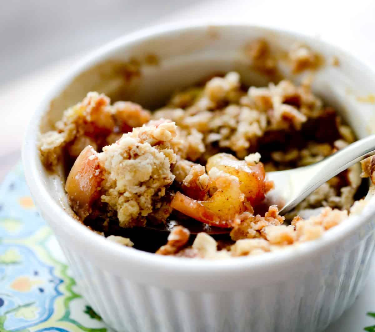 Microwave apple crisp dessert in small white ramekin with fork.