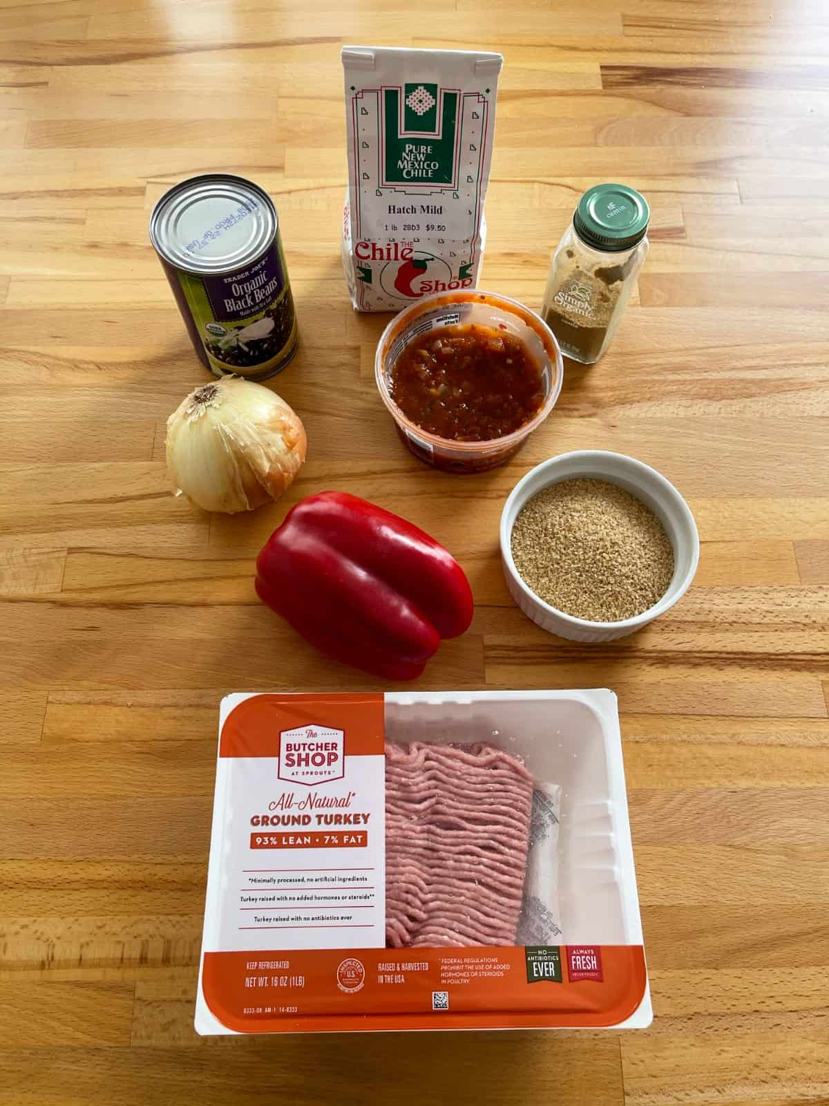 Ingredients for making taco casserole including ground turkey, black beans, salsa, onion, chili powder, cumin and bulgur.