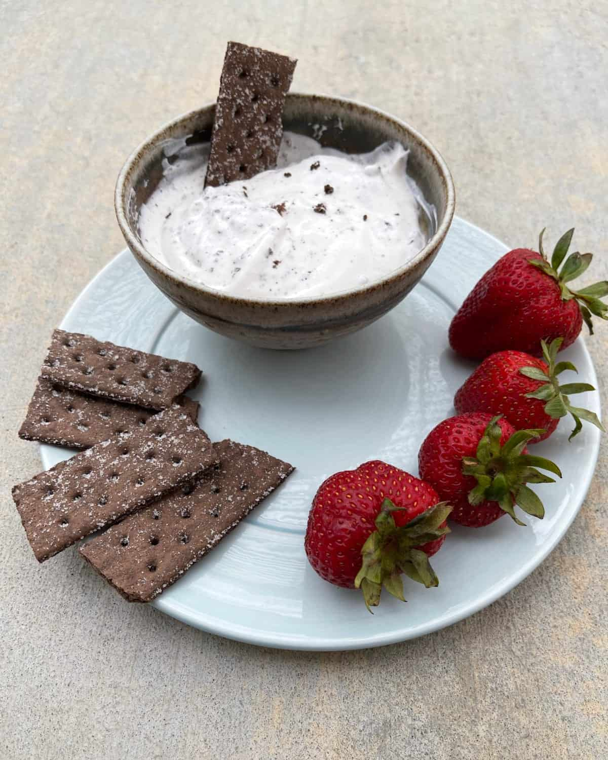 Bowl of cookies 'n cream dip with small plate of chocolate graham crackers and fresh strawberries