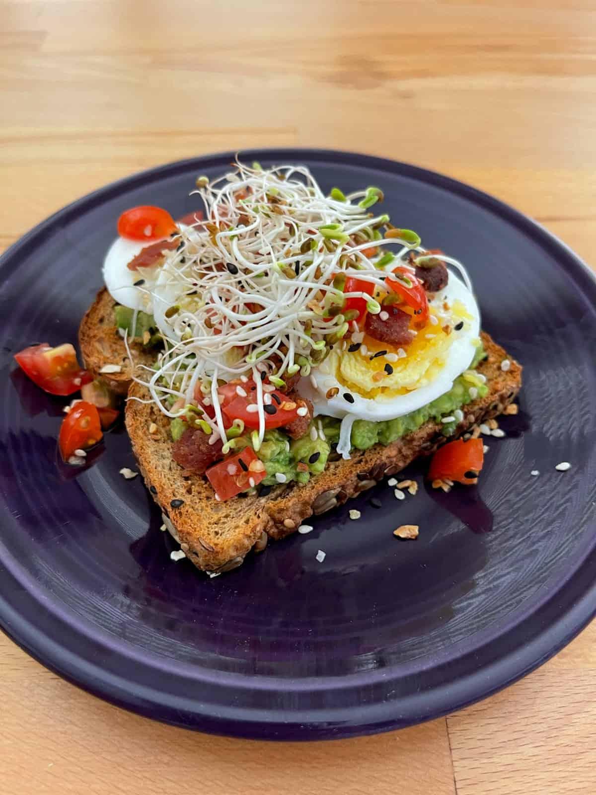 BLT avocado toast on purple plate on wood table