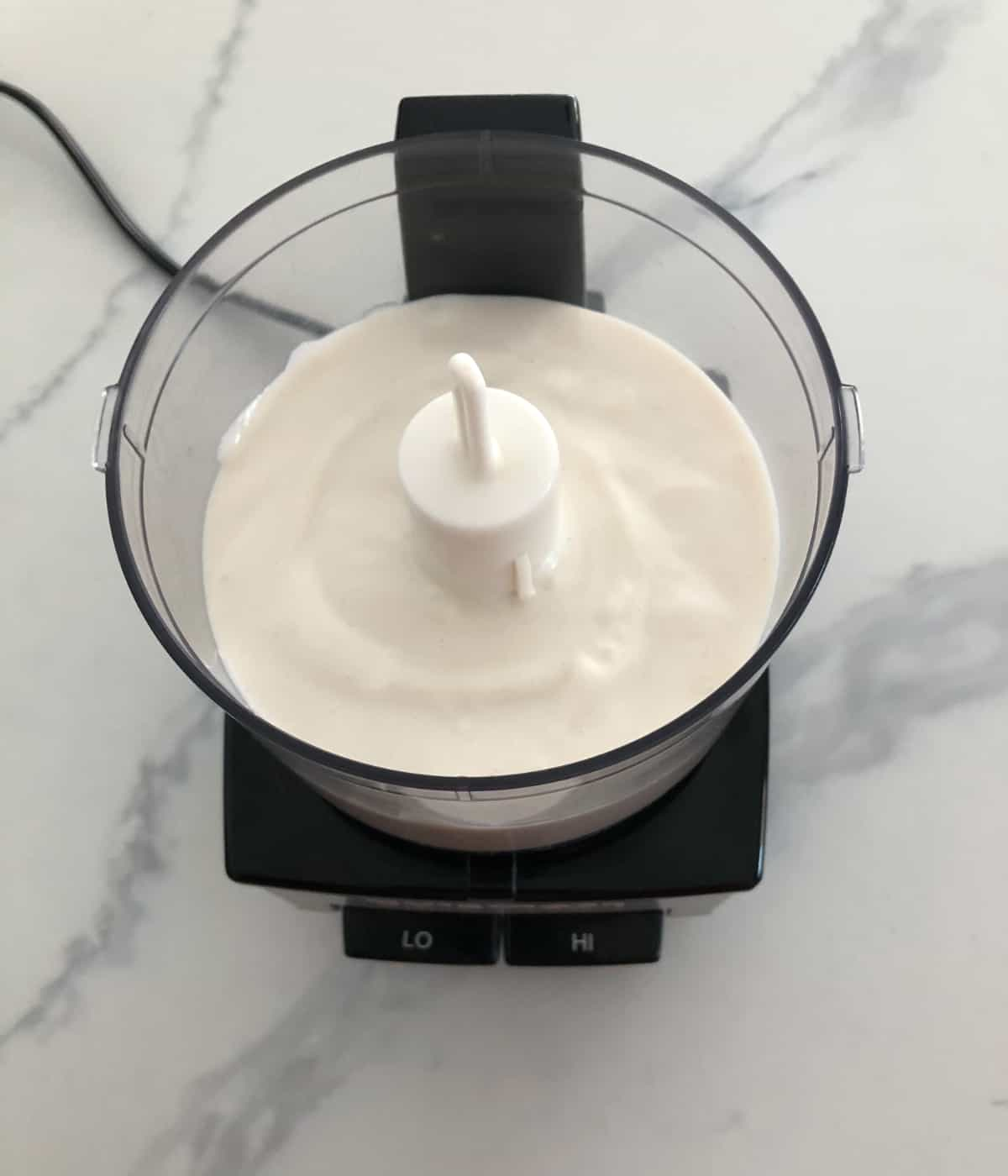 Pureeing cottage cheese, vanilla and honey in food processor.