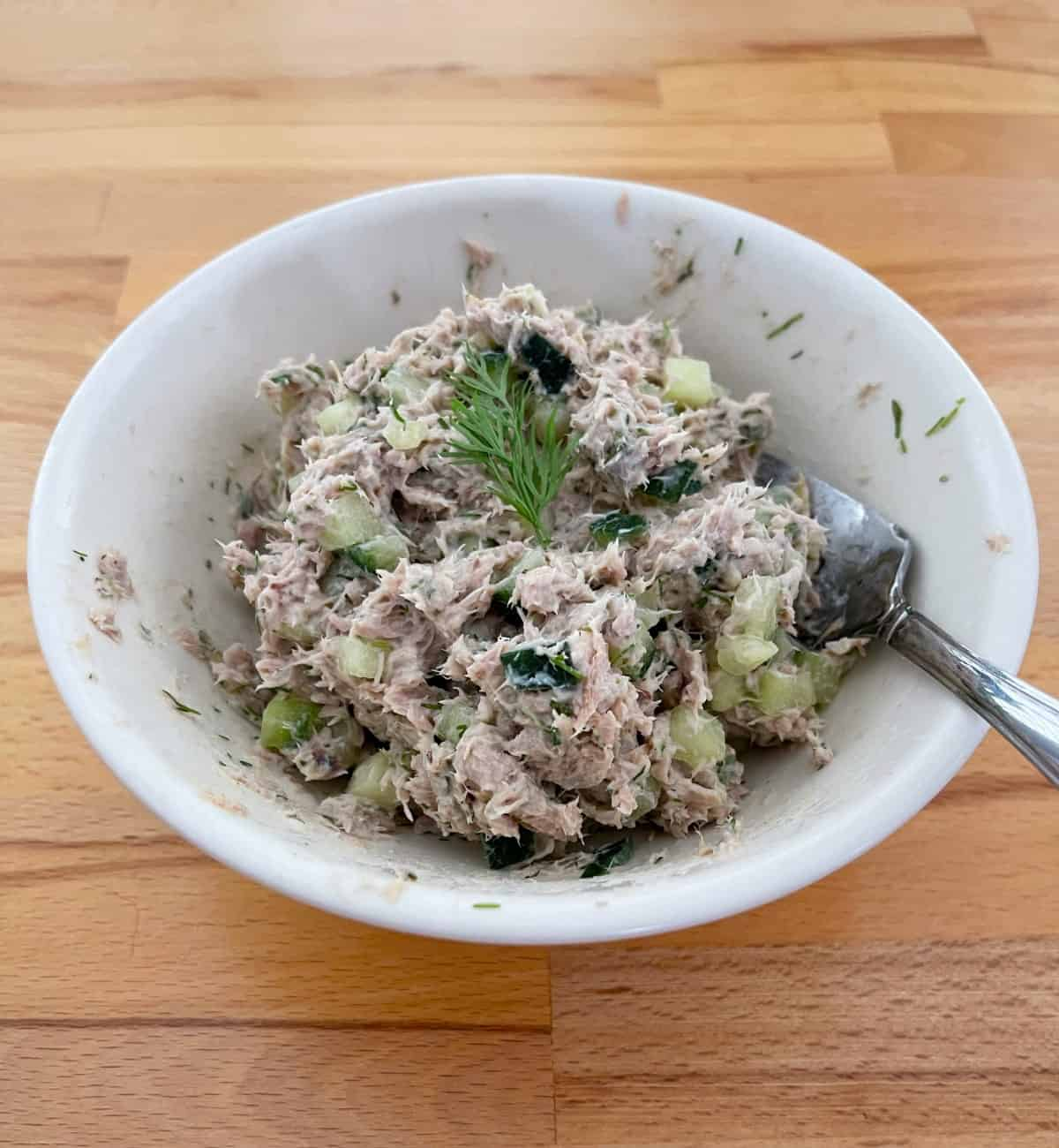 Tuna Dill Spread in white bowl with fork and fresh dill garnish.