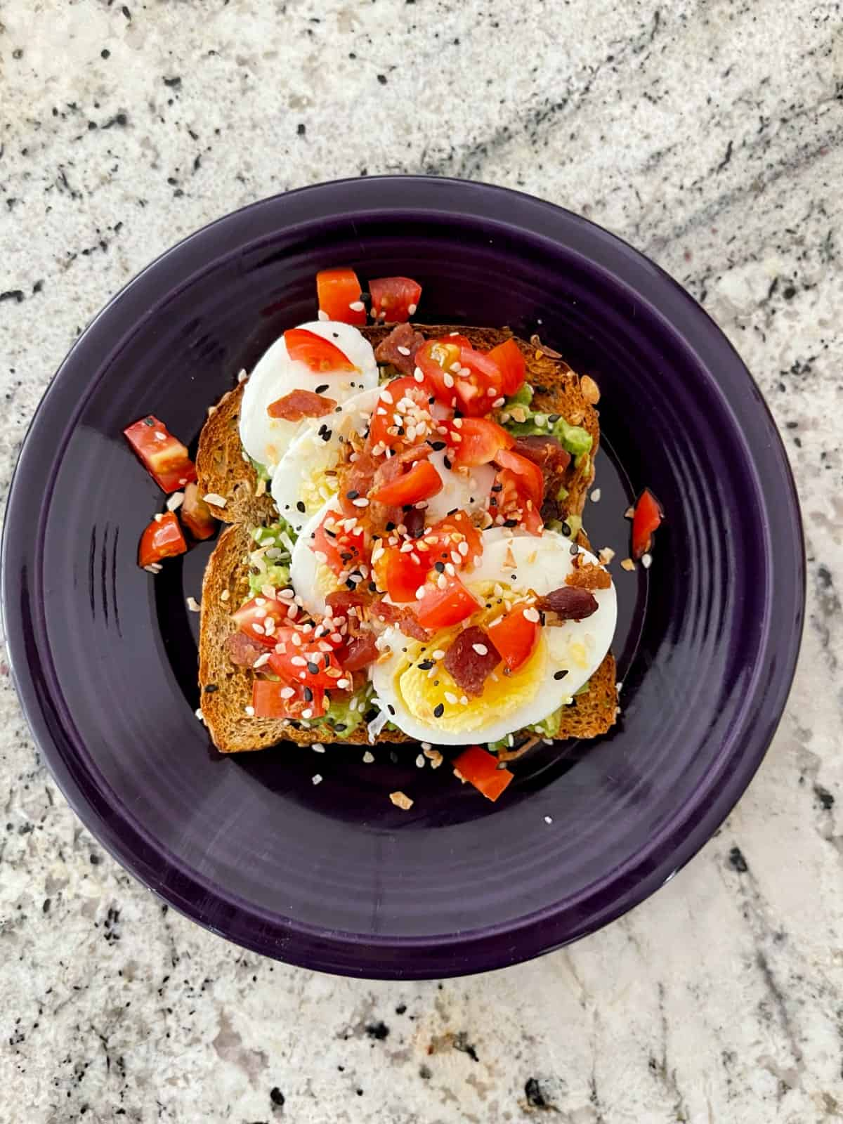 Avocado toast topped with boiled egg slices, bacon, tomato and everything bagel seasoning