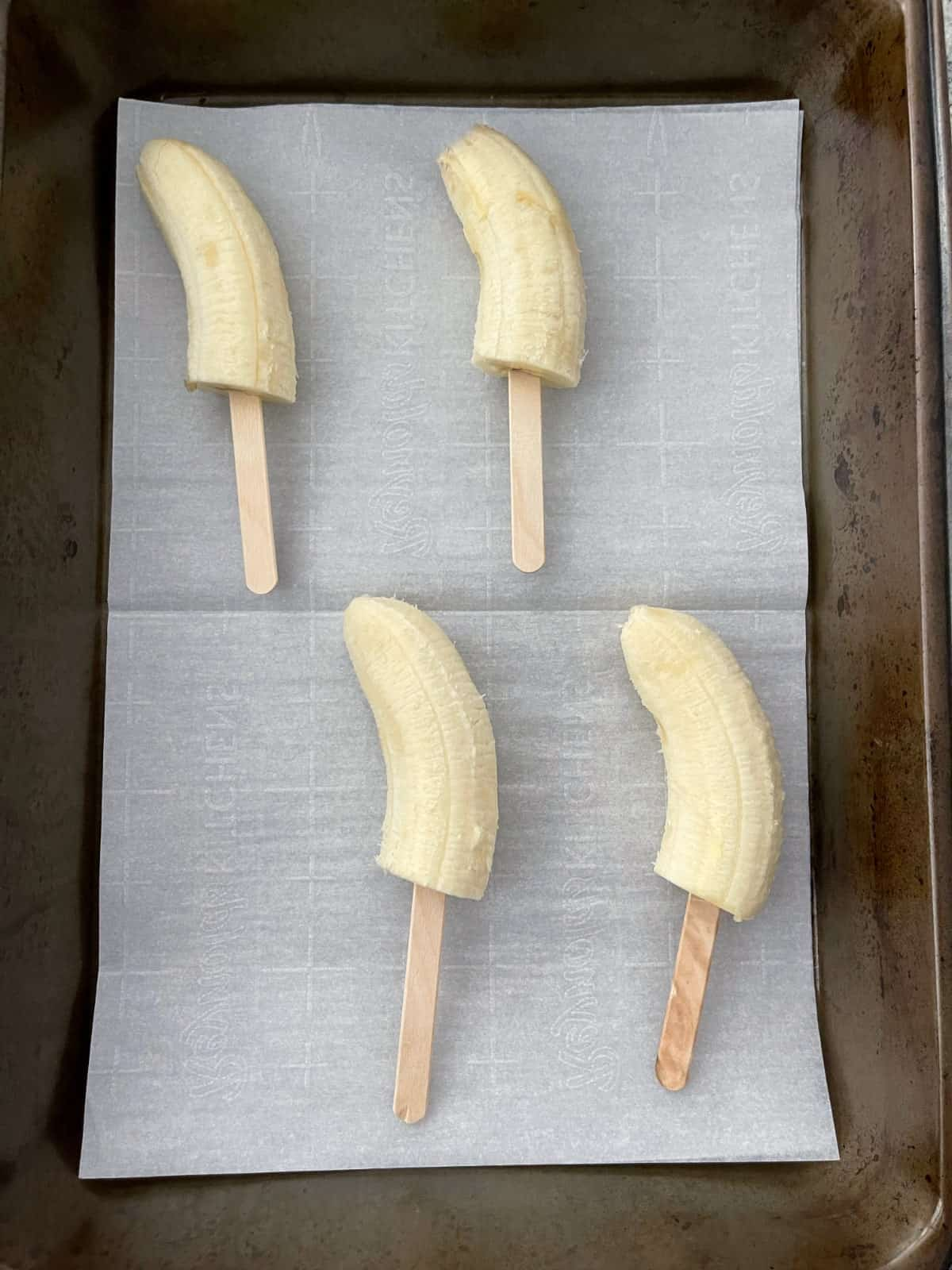 Peeled bananas cut in half on wooden popsicle sticks in parchment lined pan.