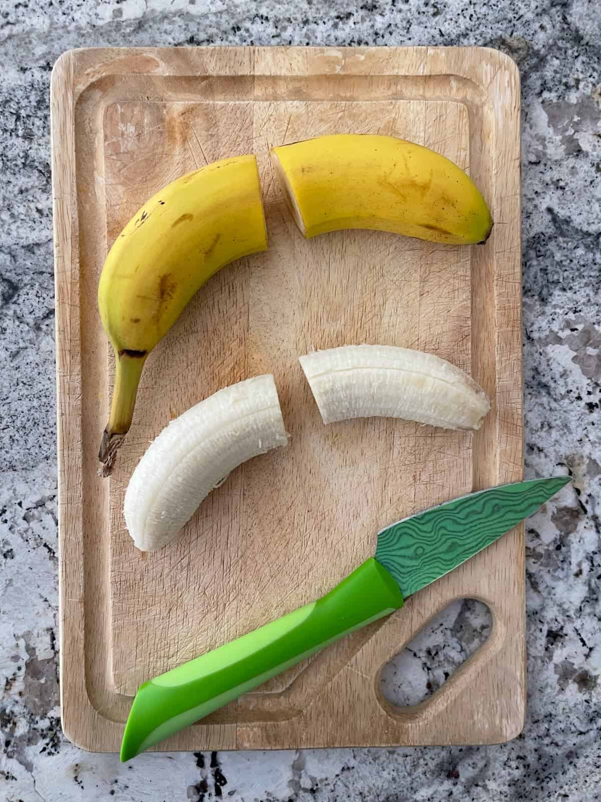 Two bananas on wood cutting board, one peeled the other unpeeled, with green knife.