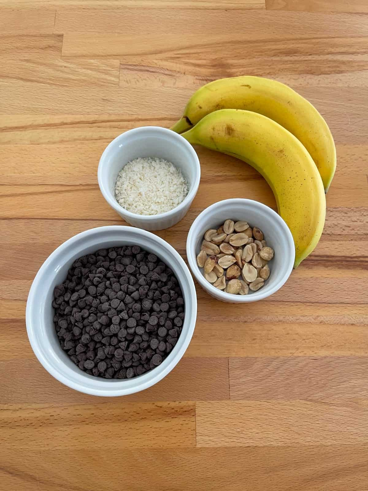 Two bananas, mini chocolate chips, shredded coconut and peanuts on wooden table.