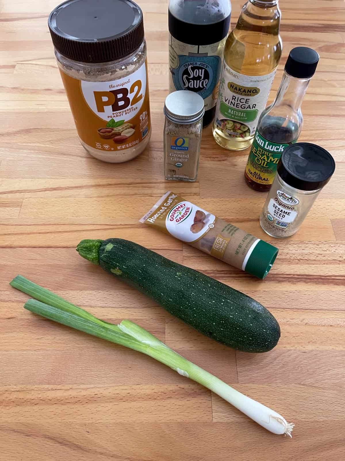 Ingredient for making sesame zoodles, including powdered peanut butter, soy sauce, rice vinegar, sesame oil, zucchini, garlic, ginger and green onion.