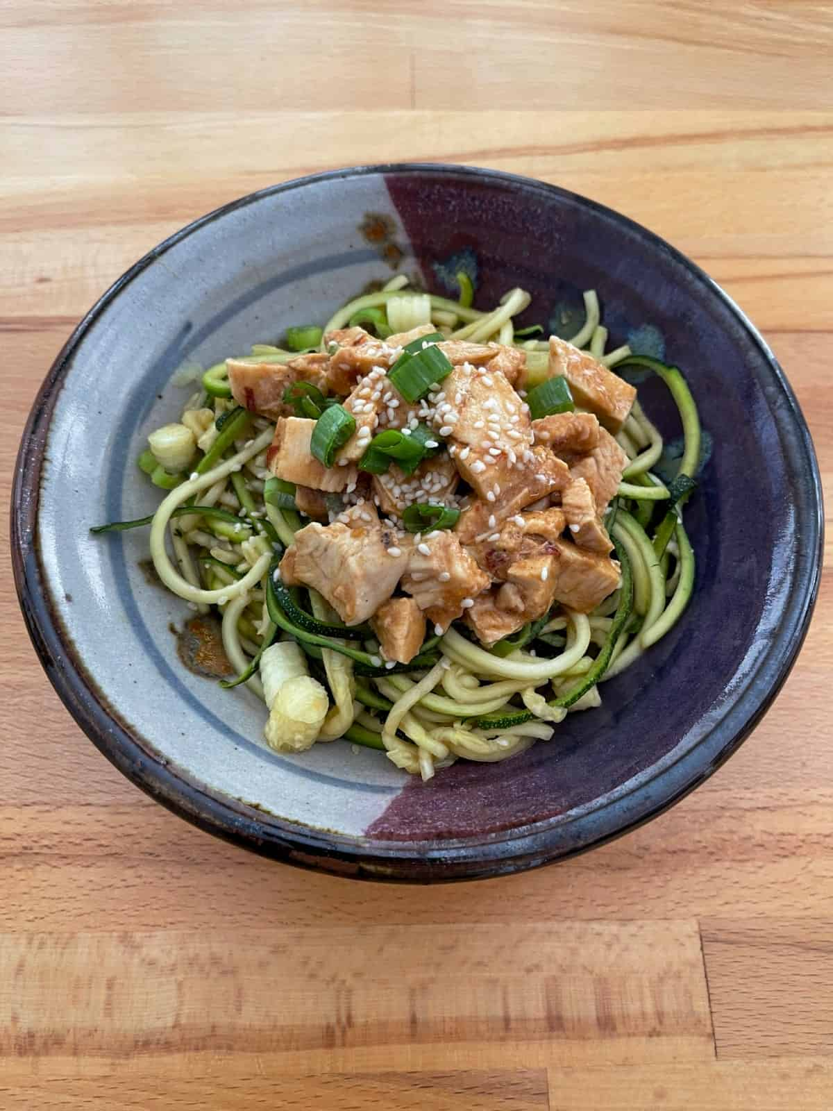 Sesame zucchini noodles with chicken in ceramic bowl on wood table.