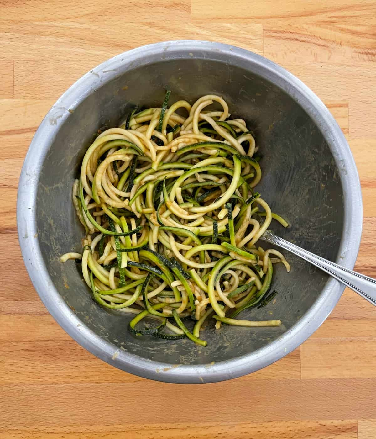 Tossing Asian-inspired sesame zucchini noodles with sauce in mixing bowl.