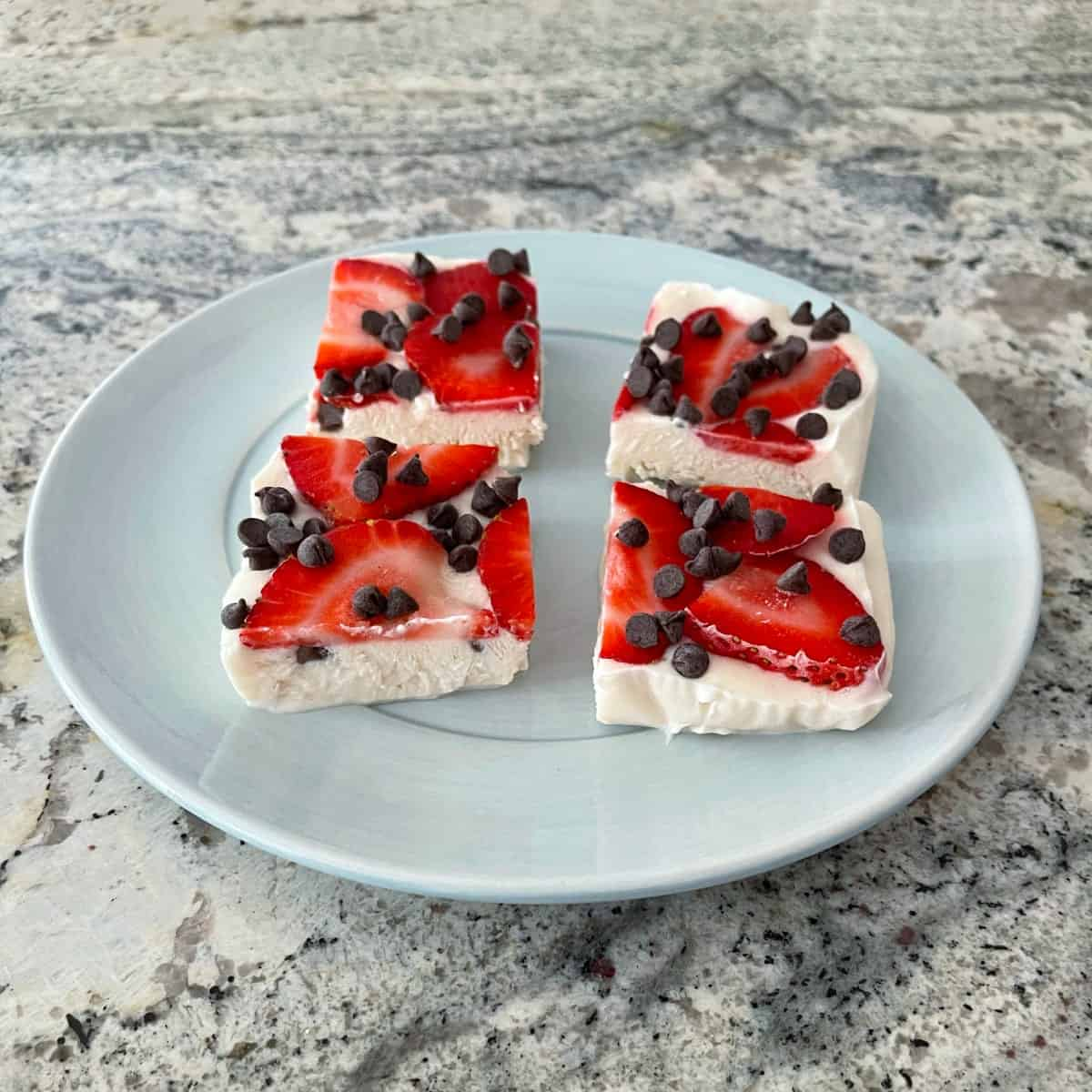 Four pieces strawberry chocolate chip frozen greek yogurt bark on blue plate on granite counter.